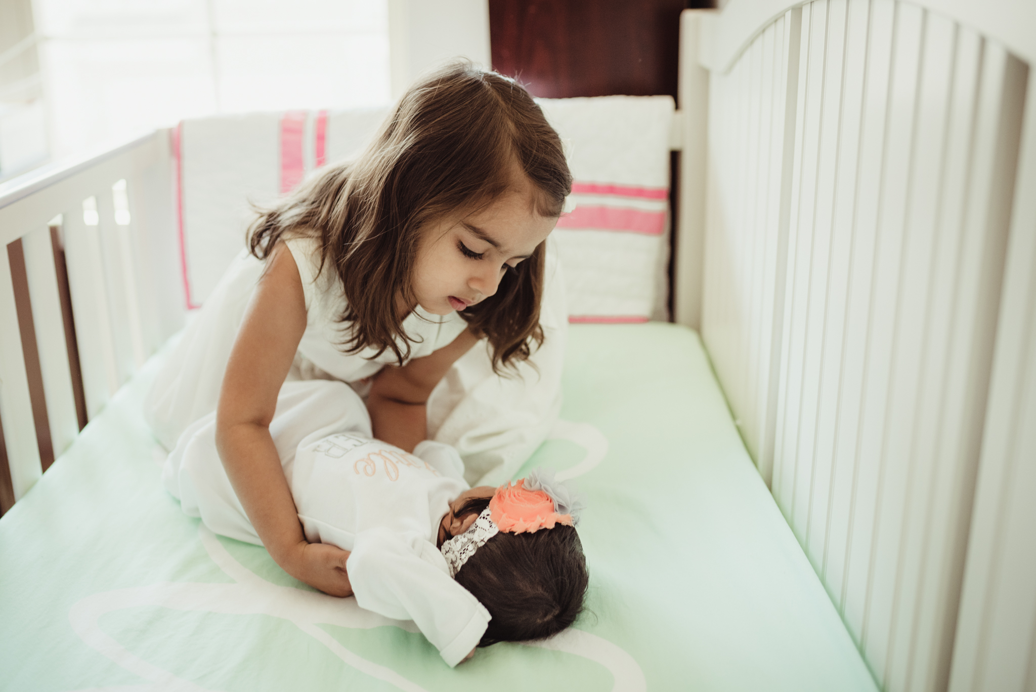The newborn baby girl lay in her crib with her big sister during her lifestyle newborn session with Rose Trail Images in Raleigh, North Carolina.