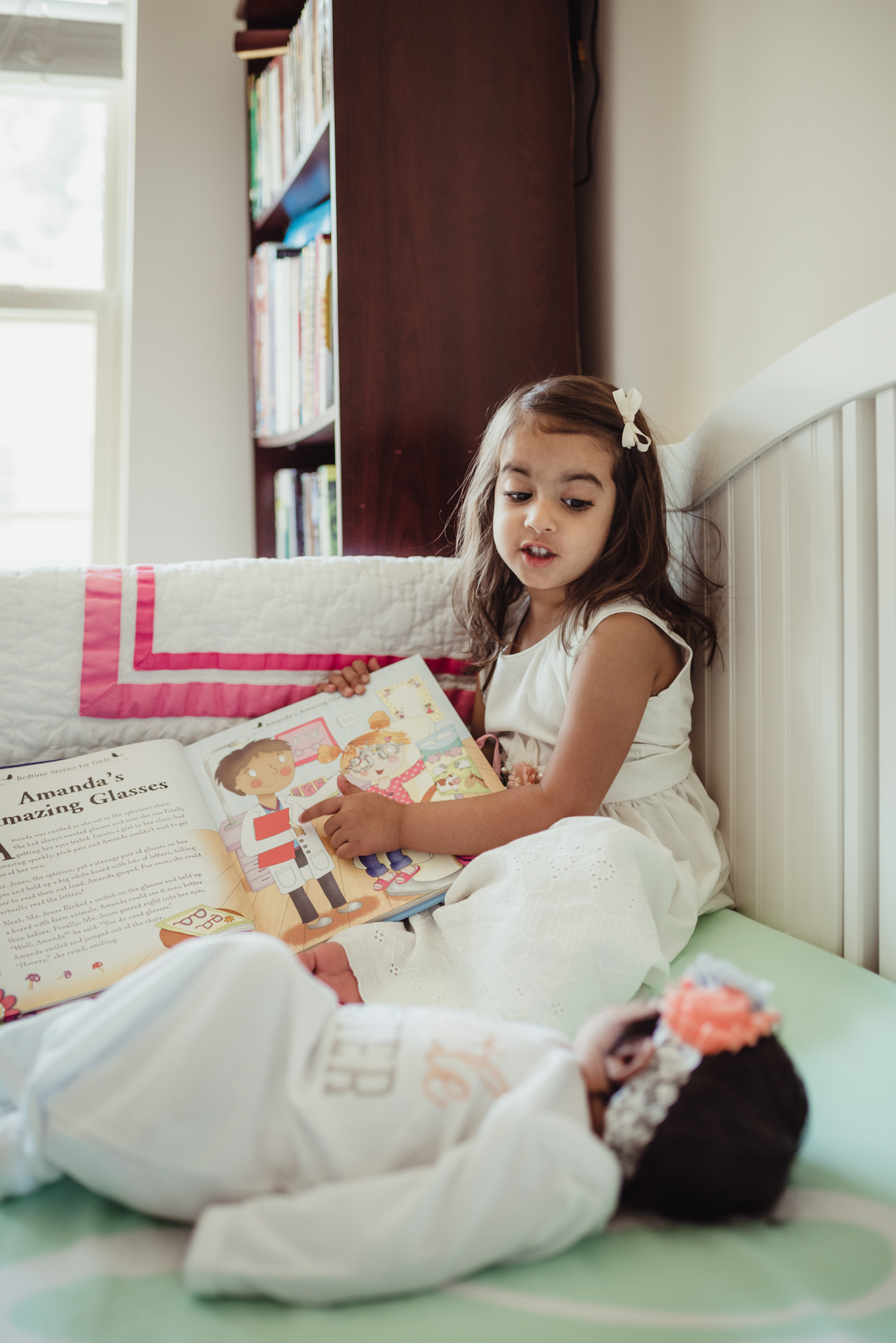 The big sister read a book to her baby sister in the crib during her lifestyle newborn session with Rose Trail Images in Raleigh, North Carolina.