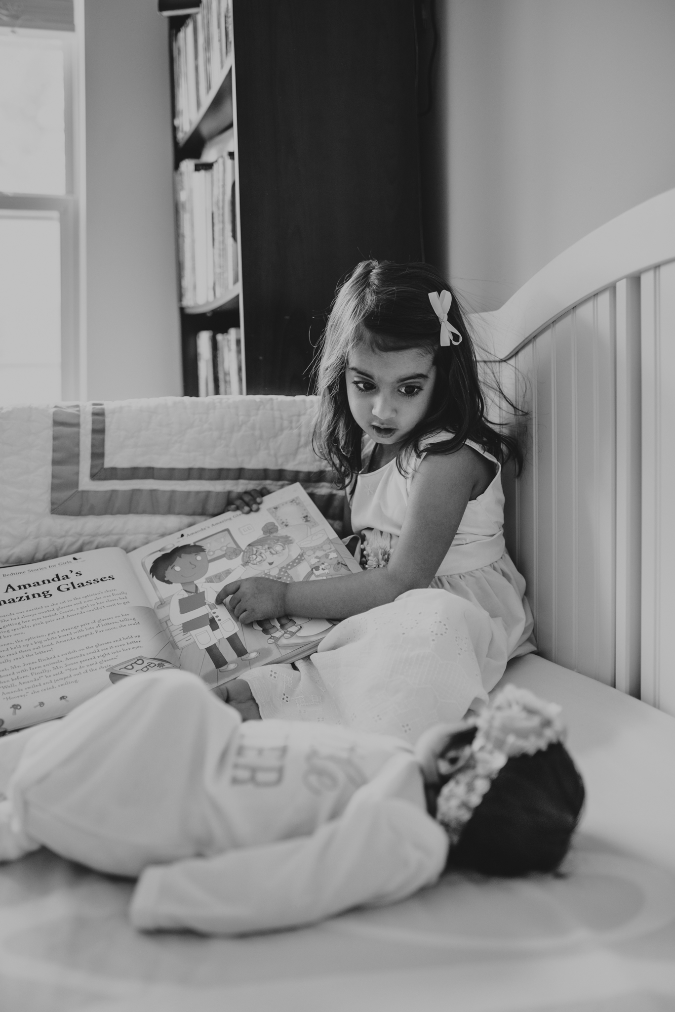 The big sister read a book to her baby sister while sitting in the crib during her lifestyle newborn session with Rose Trail Images in Raleigh, North Carolina.