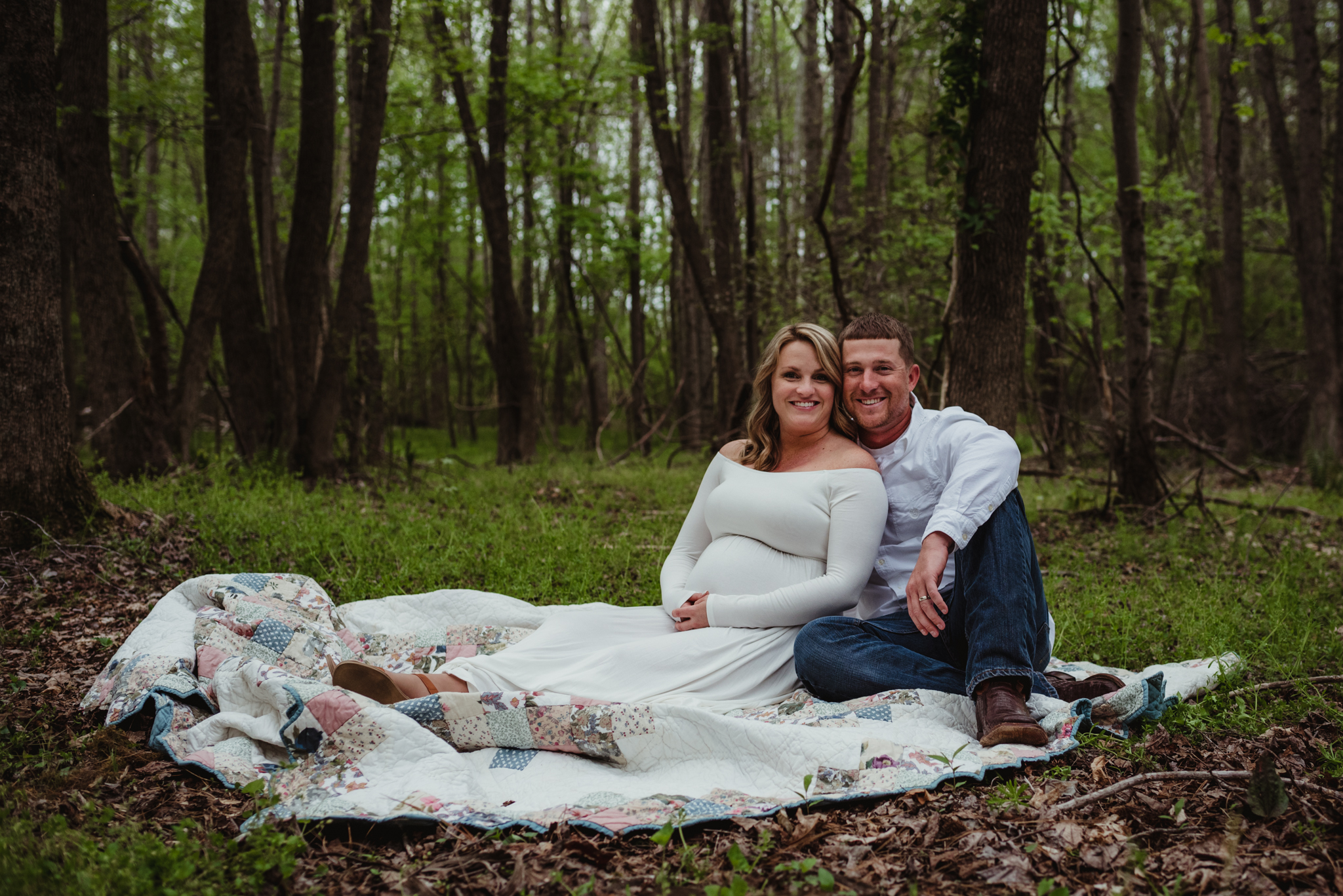The soon to be parents cozy up on the blanket in the woods at sunset in Rolesville, NC for Rose Trail Images.