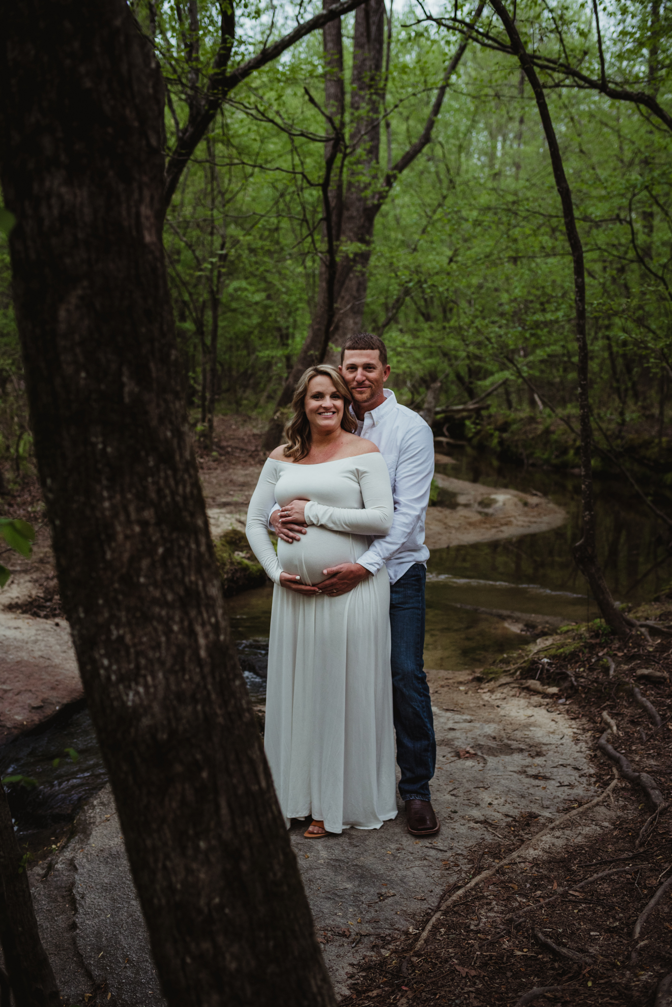 The soon to be parents stand together by the creek during their maternity shoot with Rose Trail Images at Mill Bridge Nature Park in Rolesville, NC.