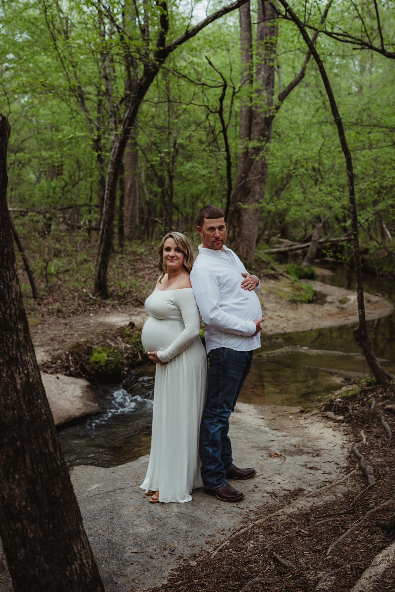 The soon to be parents show off both their bellies during their maternity shoot with Rose Trail Images at Mill Bridge Nature Park in Rolesville, NC.