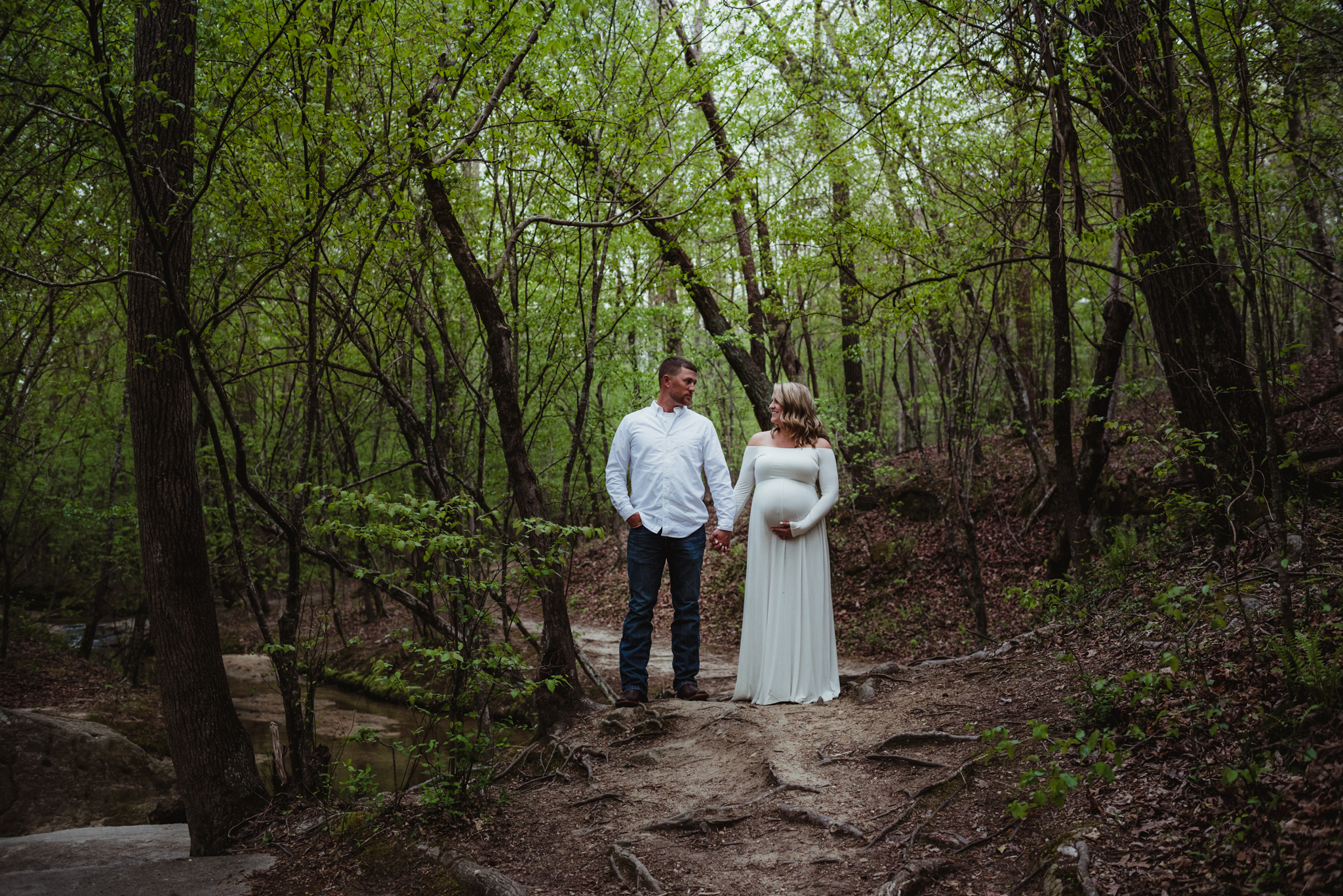 The soon to be parents stand side by side on the wooded trail during their maternity shoot with Rose Trail Images at Mill Bridge Nature Park in Rolesville, NC.