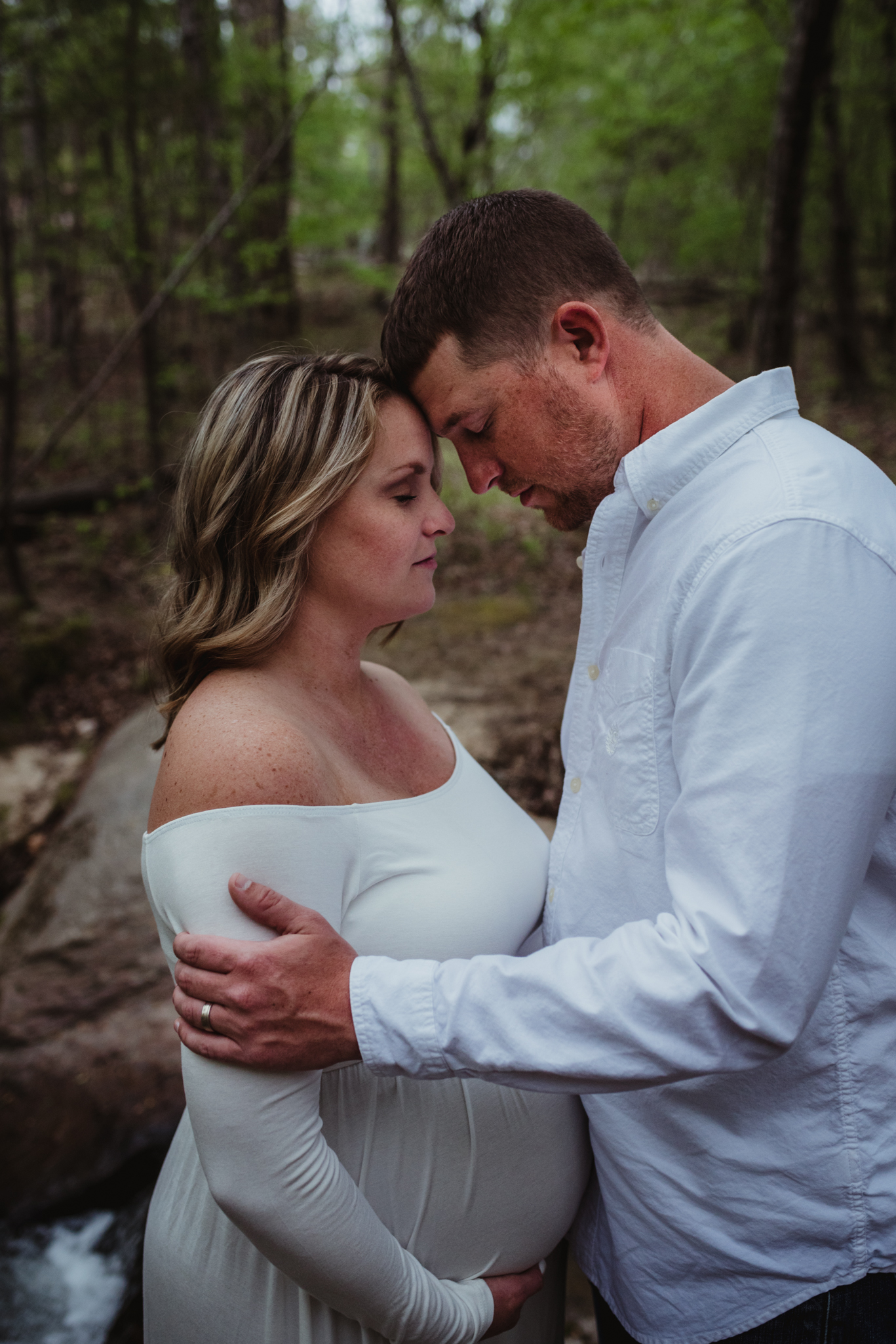 The soon to be parents hold each other close during their maternity shoot with Rose Trail Images at Mill Bridge Nature Park in Rolesville, NC.
