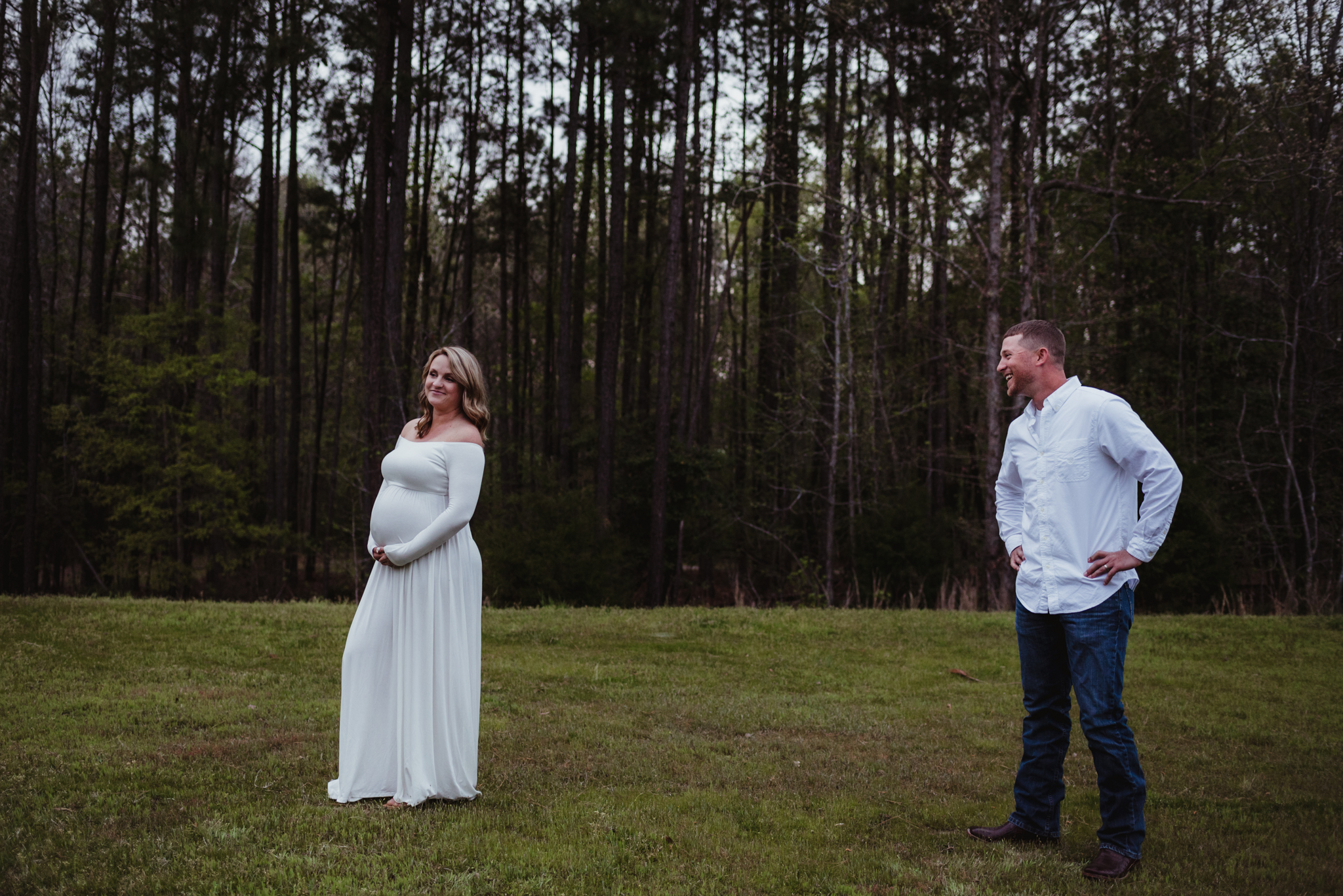 The soon to be parents tease each other during their maternity shoot with Rose Trail Images at Mill Bridge Nature Park in Rolesville, NC.