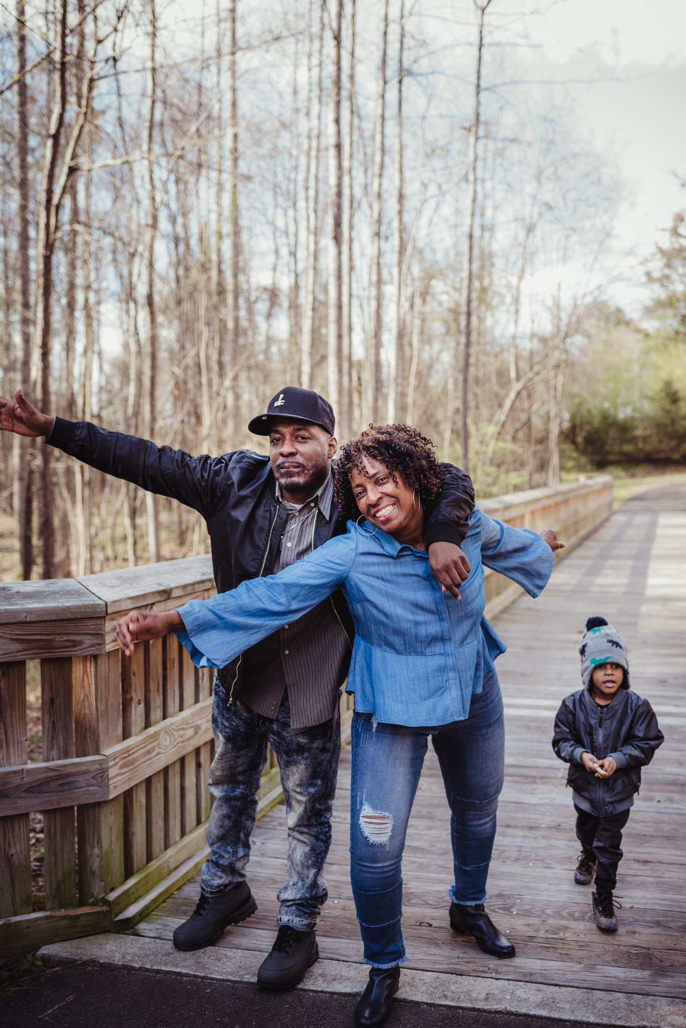 Mom poses for Rose Trail Images with her middle adult son and grandson in Rolesville Main Street Park.
