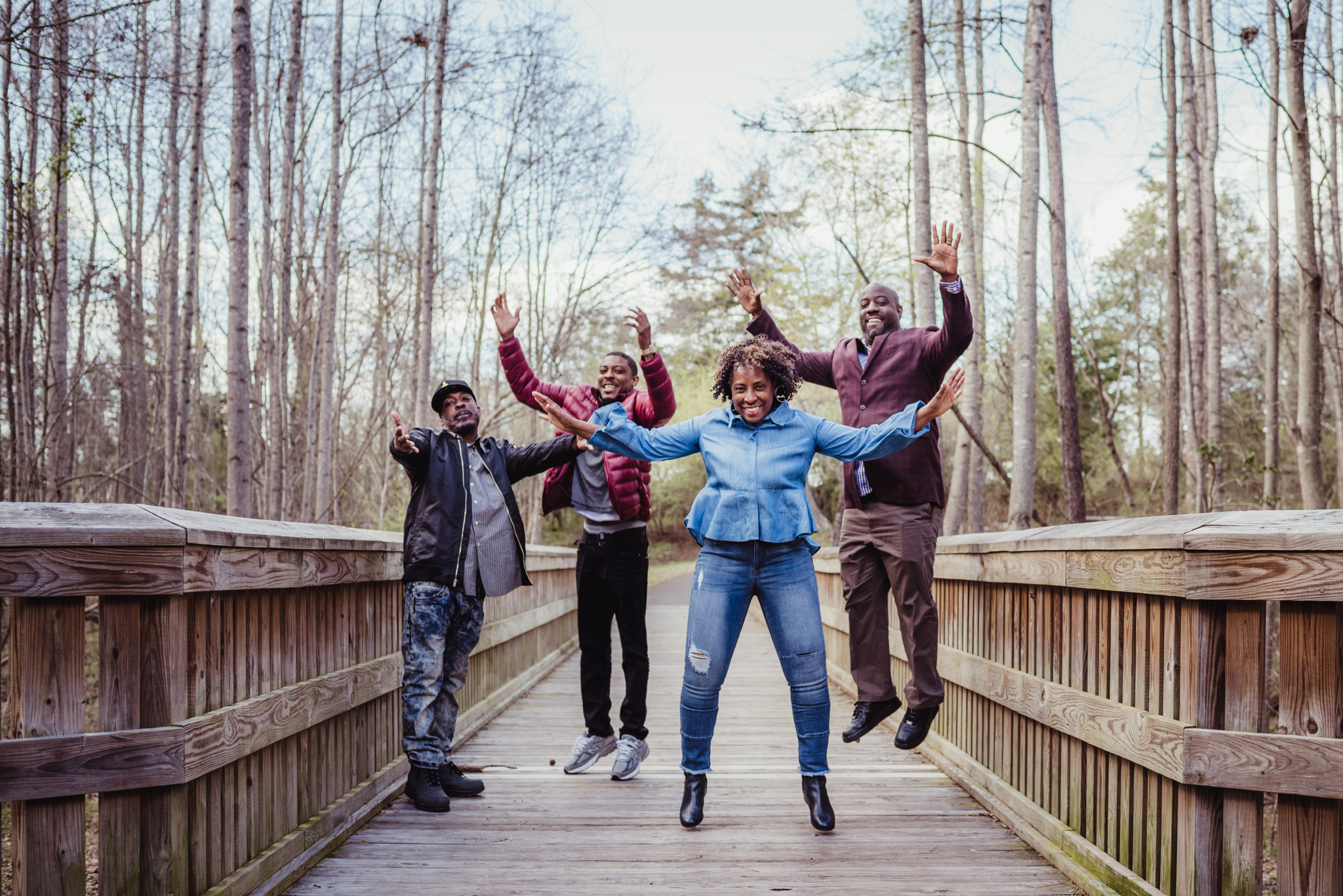 Mom and her adult sons jump for joy on the wooden bridge in Rolesville Main Street Park during their family photo session with Rose Trail Images.