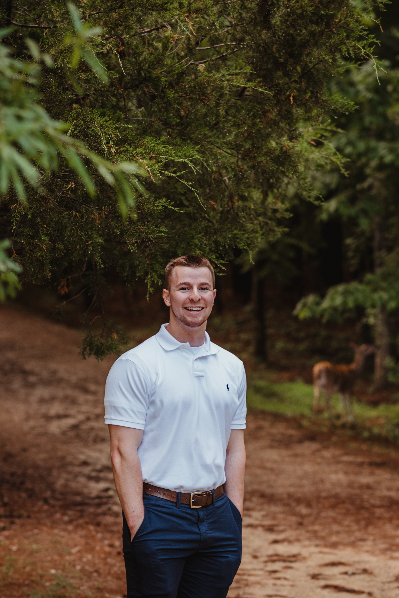 Harrison, with a deer behind him, had his senior portraits done at Durant Nature Preserve in Raleigh, NC by Rose Trail Images.