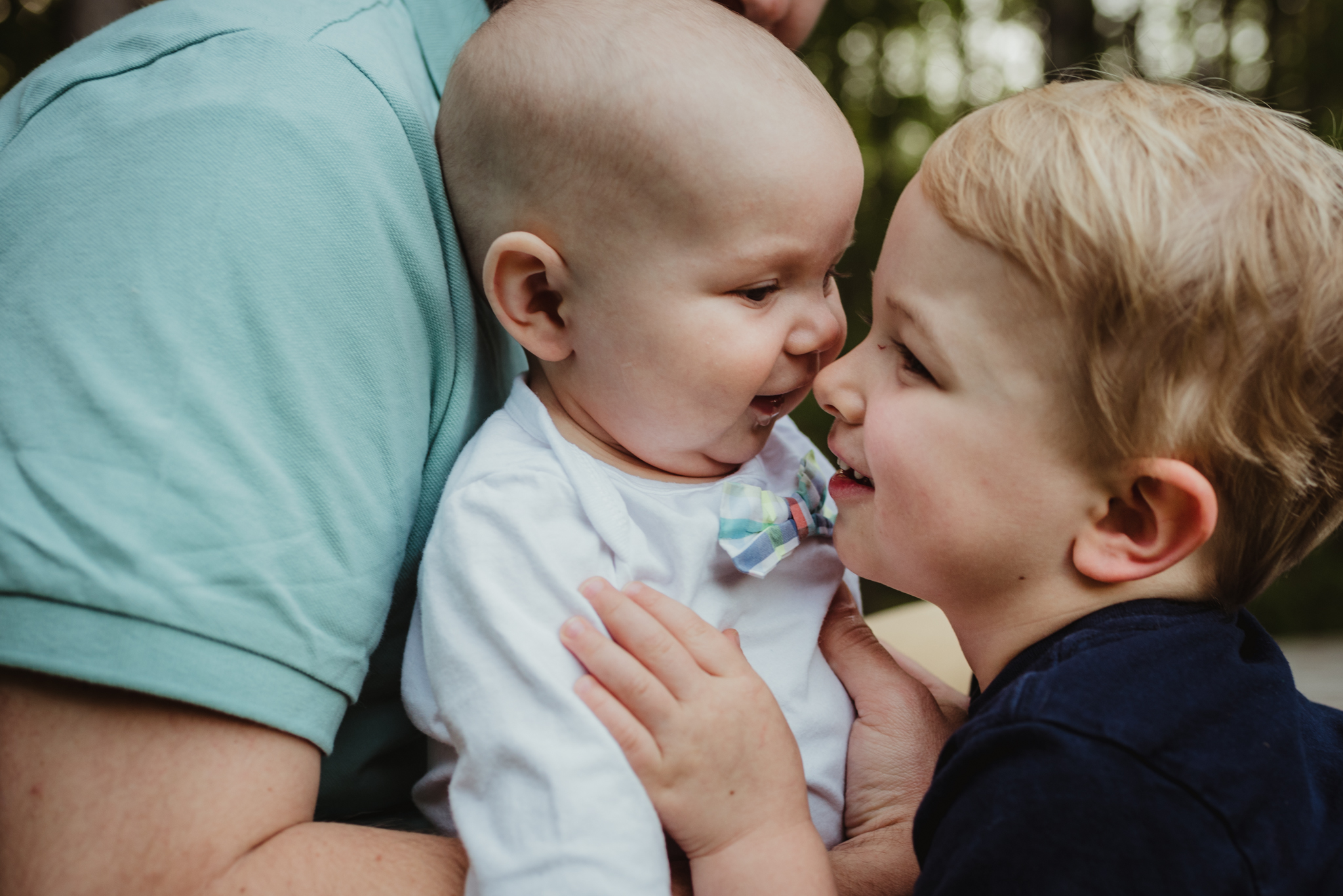 This baby brother kisses his big brother during their family photo session with Rose Trail Images in Rolesville, North Carolina.
