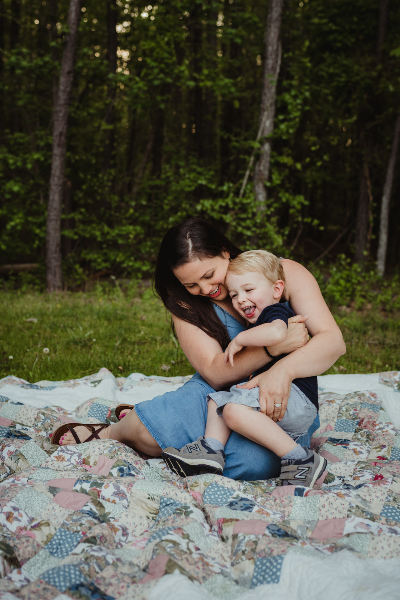 Mommy snuggles with older brother during their family photo session with Rose Trail Images in Rolesville, North Carolina.