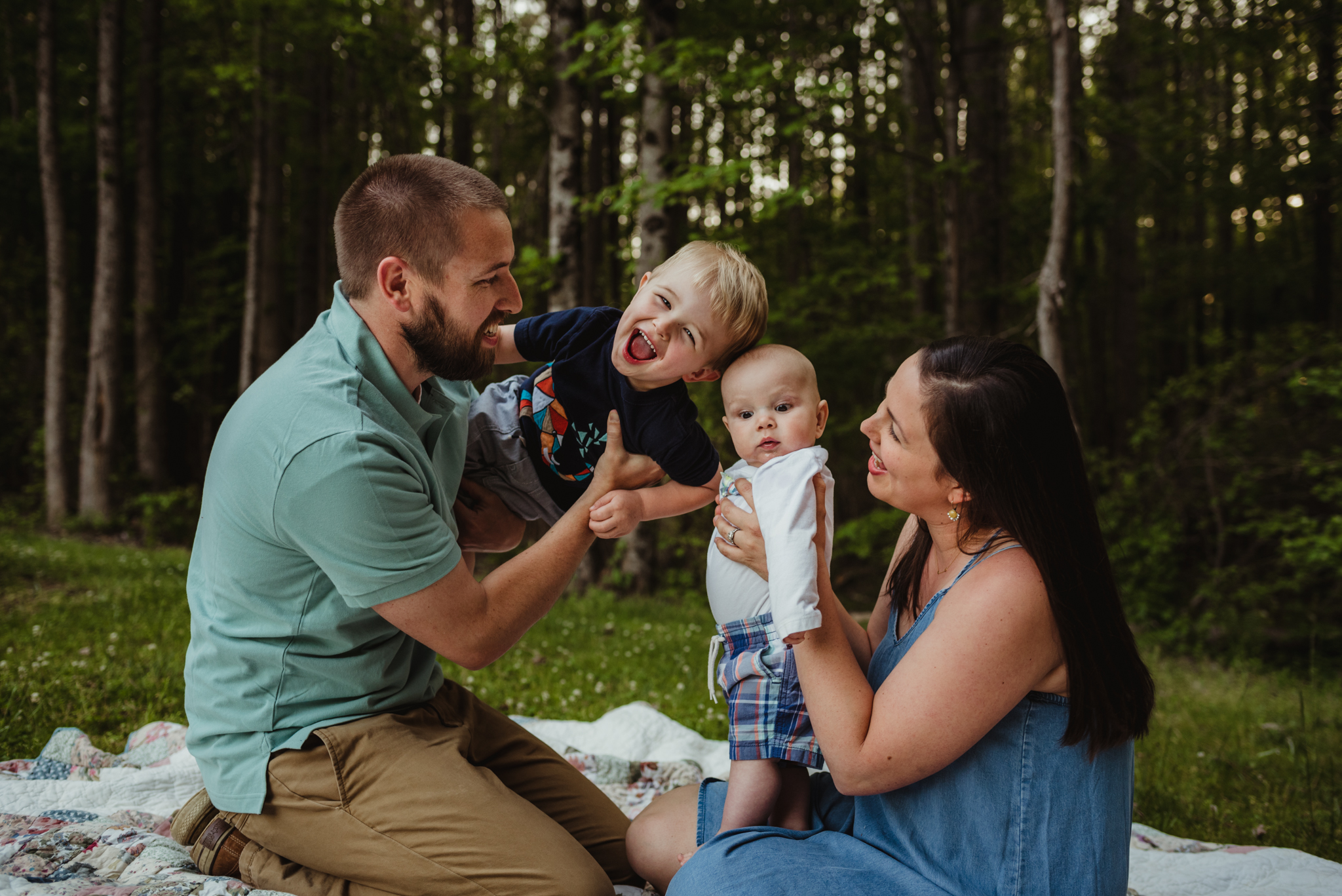 This family of four sits together on a quilt during their family photo session with Rose Trail Images in Rolesville, North Carolina.