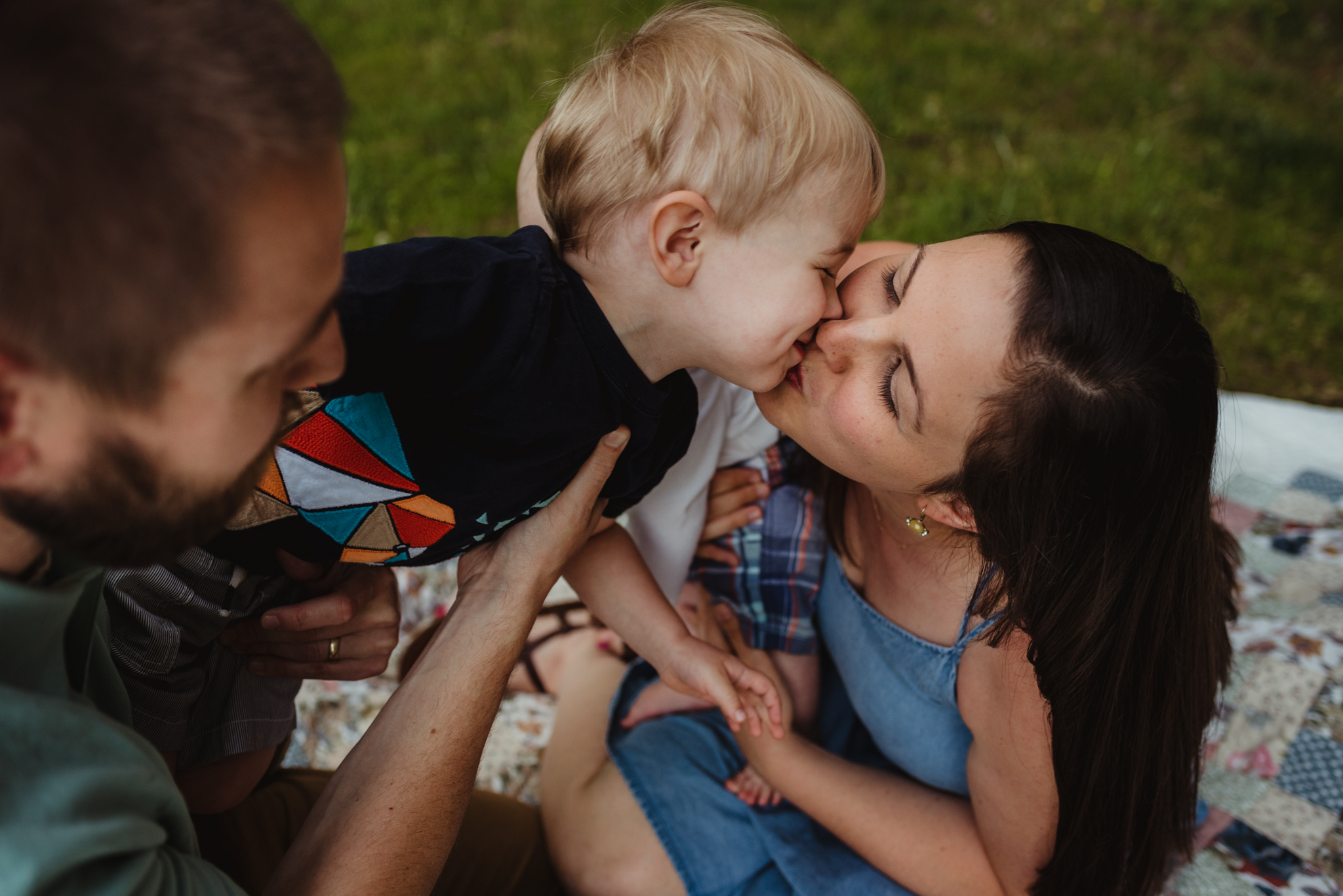Older brother kisses Mommy during their family photo session with Rose Trail Images in Rolesville, North Carolina.