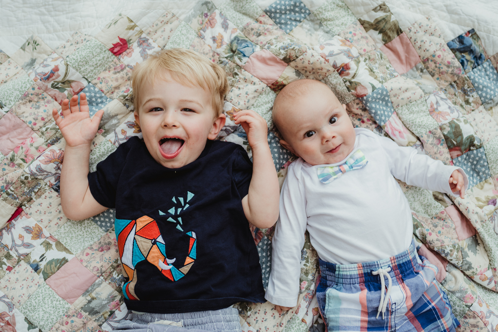Big brother and little brother lay on a quilt during their photo session with Rose Trail Images in Rolesville, North Carolina.