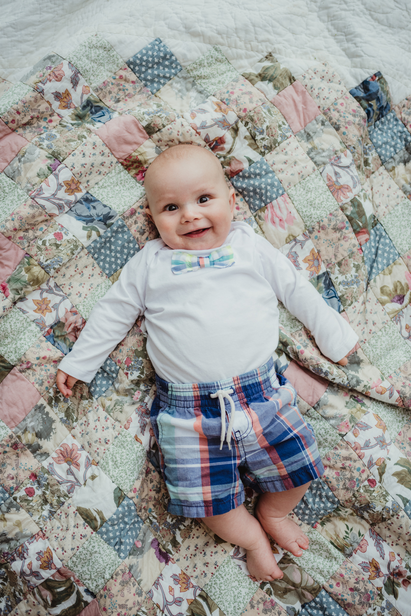 Baby brother lays and smiles on a quilt during his family's photo session with Rose Trail Images in Rolesville, North Carolina.