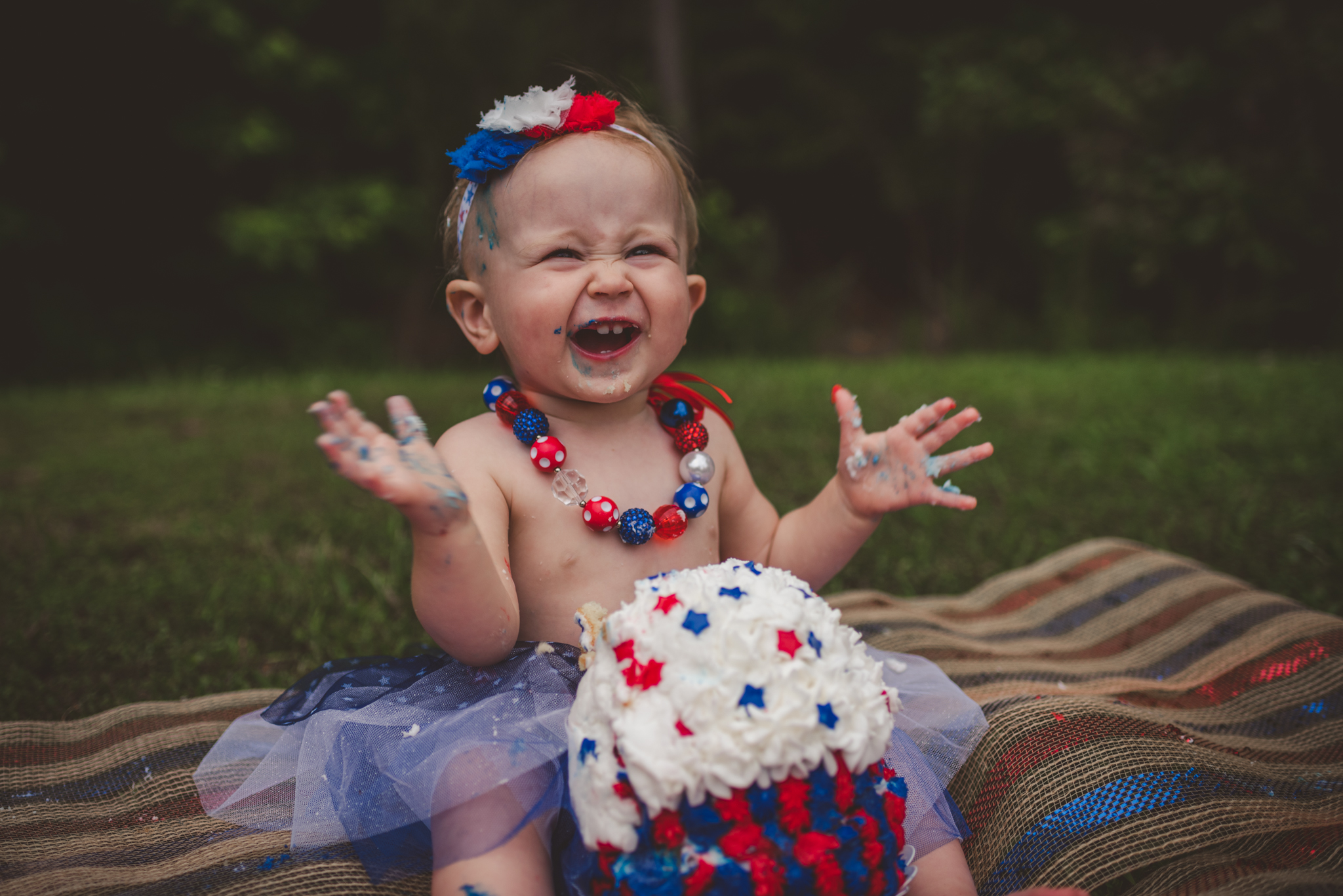 This little girl is very excited about eating her fourth of july themed smash cake for her first birthday in Rolesville, North Carolina, image taken by Rose Trail Images.