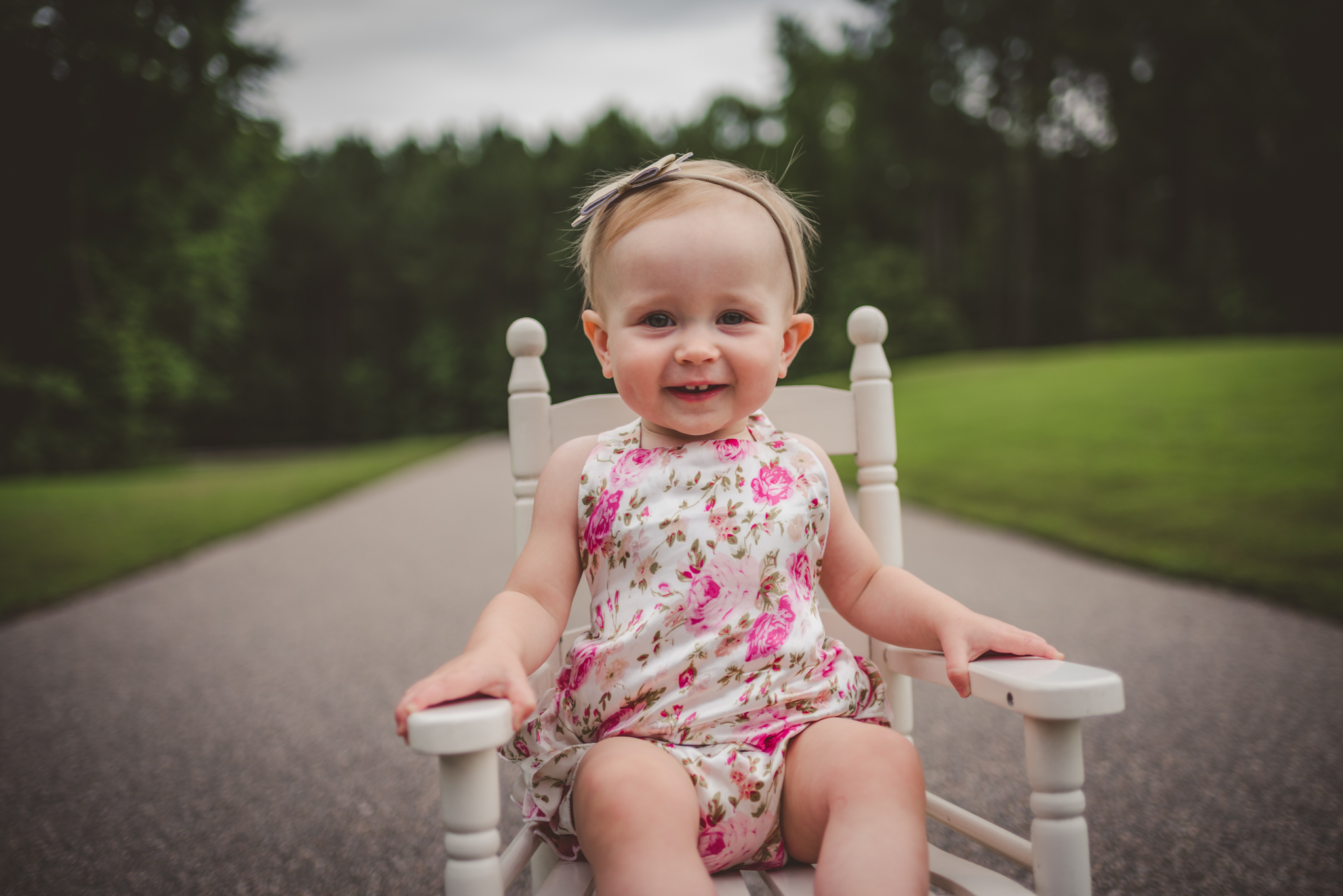 This little girl is sitting in an old rocking chair for her first birthday in Rolesville, North Carolina, image taken by Rose Trail Images.