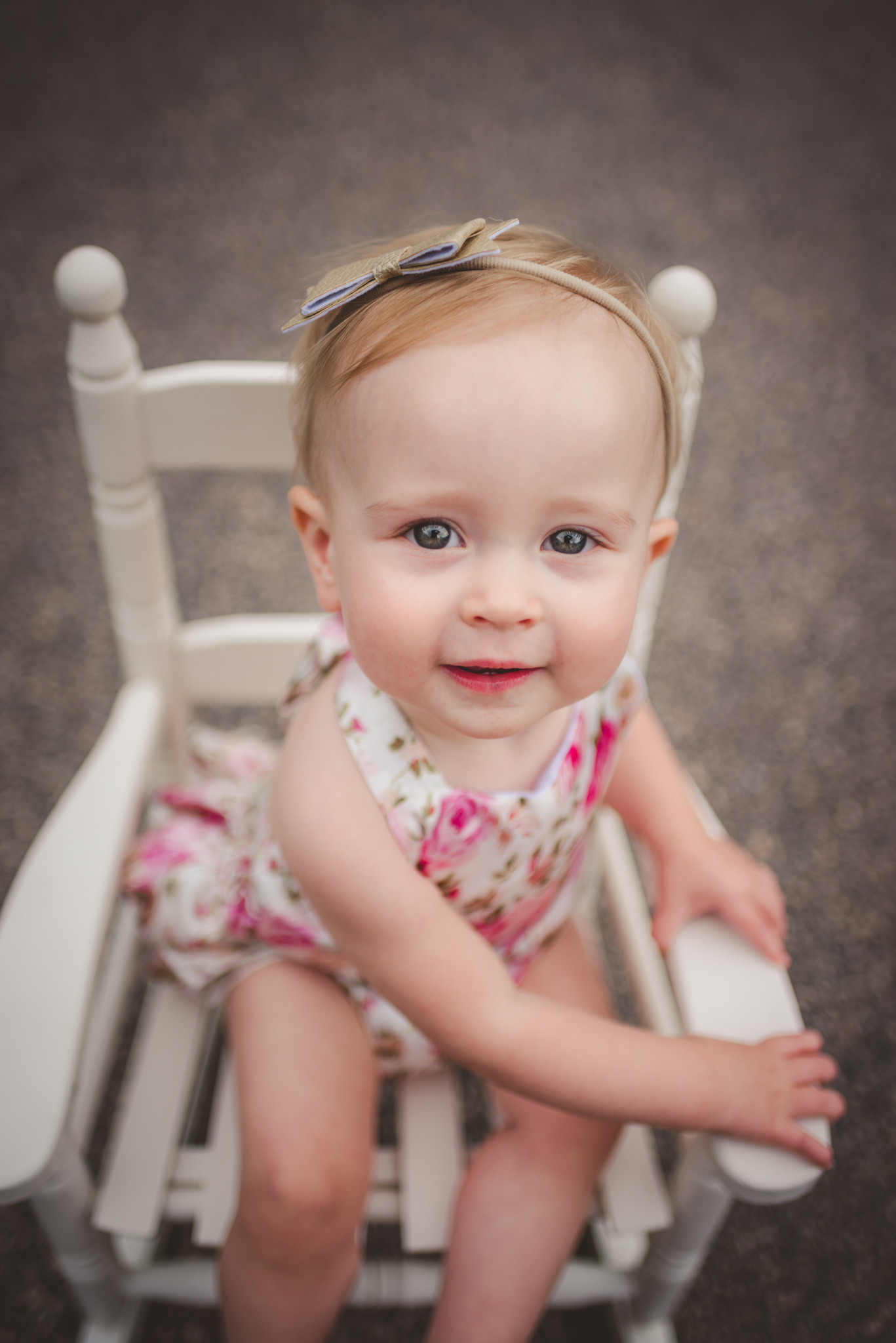 This little one year old girl is sitting in an old rocking chair for her first birthday in Rolesville, North Carolina, image taken by Rose Trail Images.