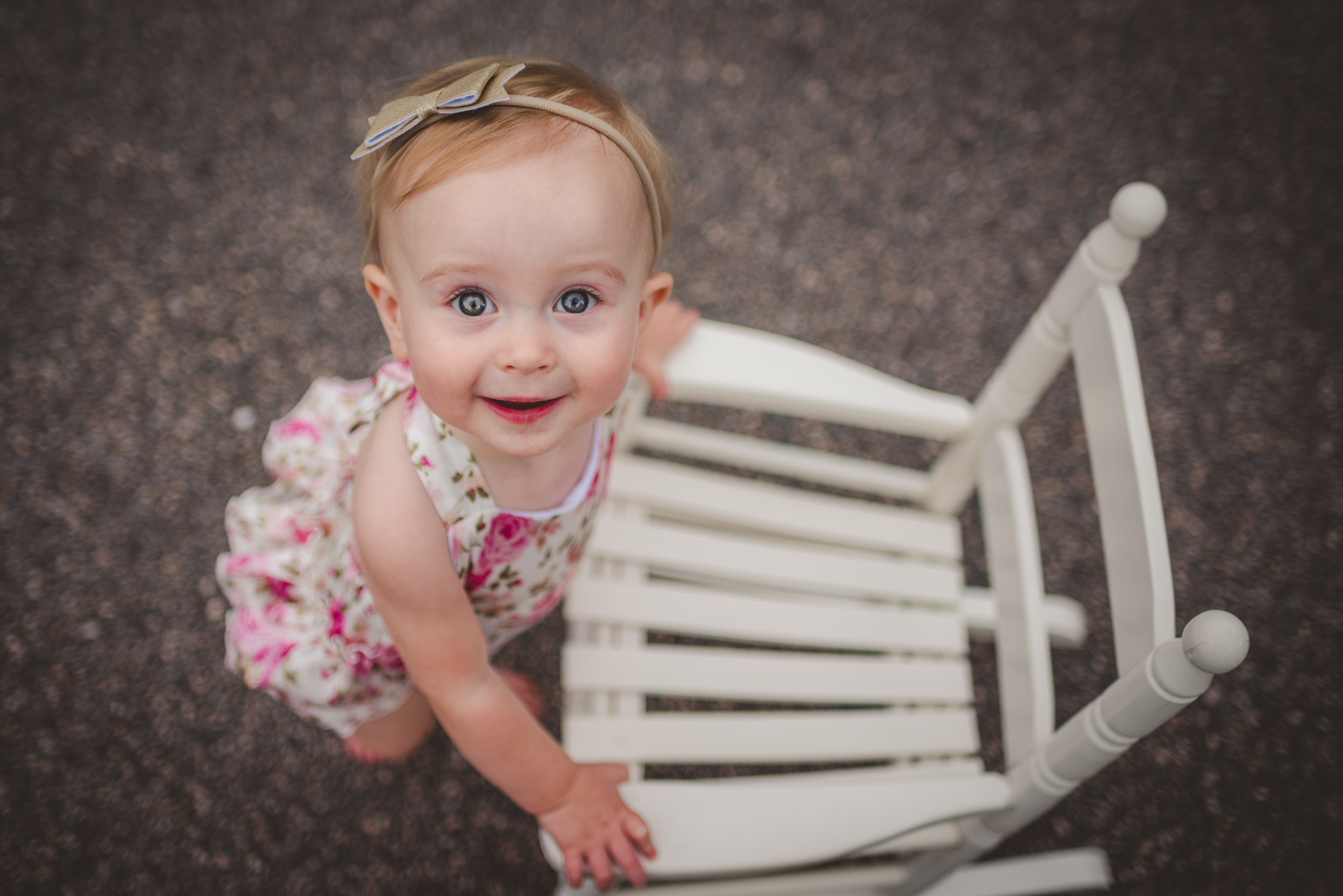 This one year old girl looks up and smiles from an old rocking chair in Rolesville, North Carolina, image taken by Rose Trail Images.