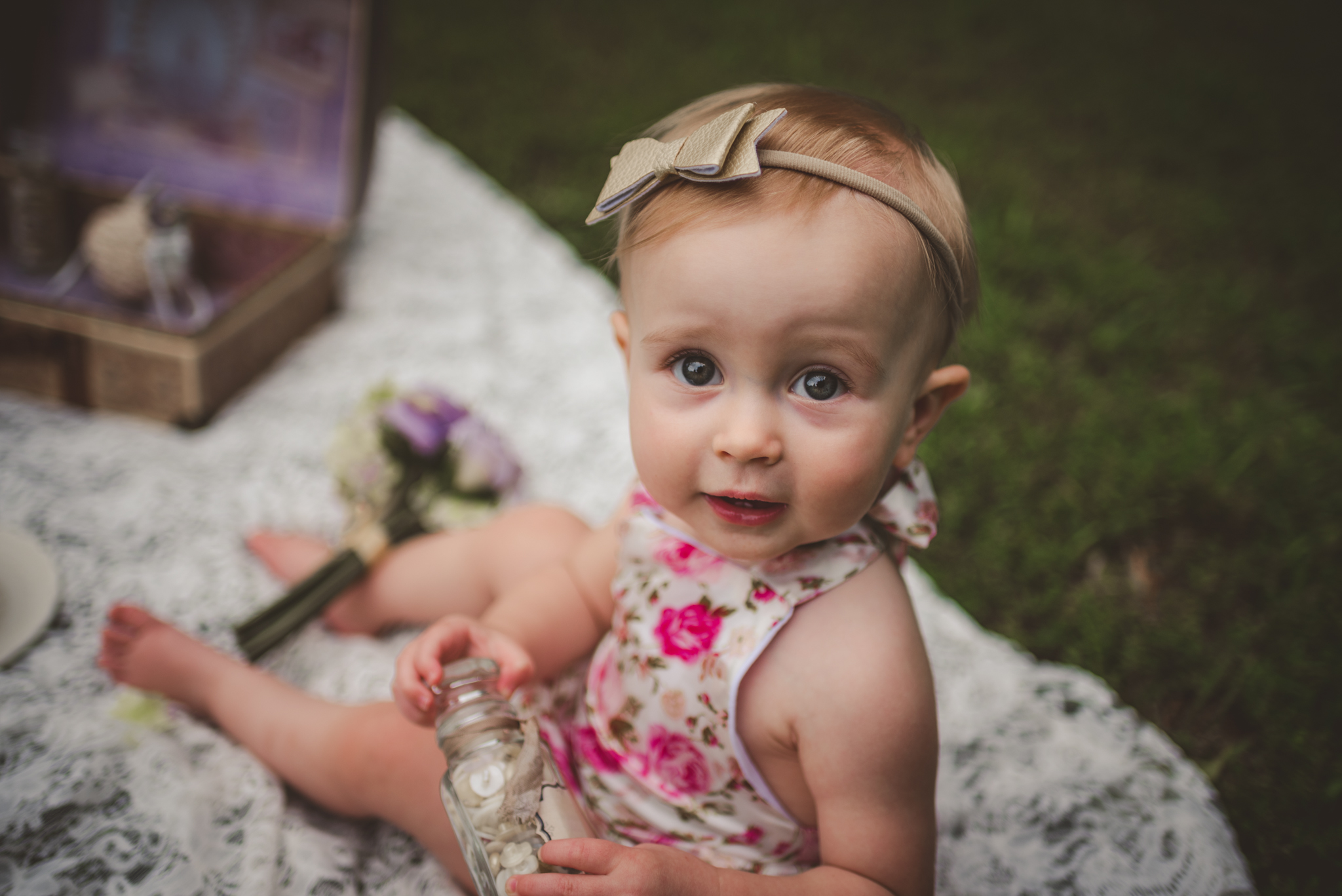 This little girl is sitting and smiling for her first birthday with vintage props from her parents wedding in Rolesville, North Carolina, image taken by Rose Trail Images.