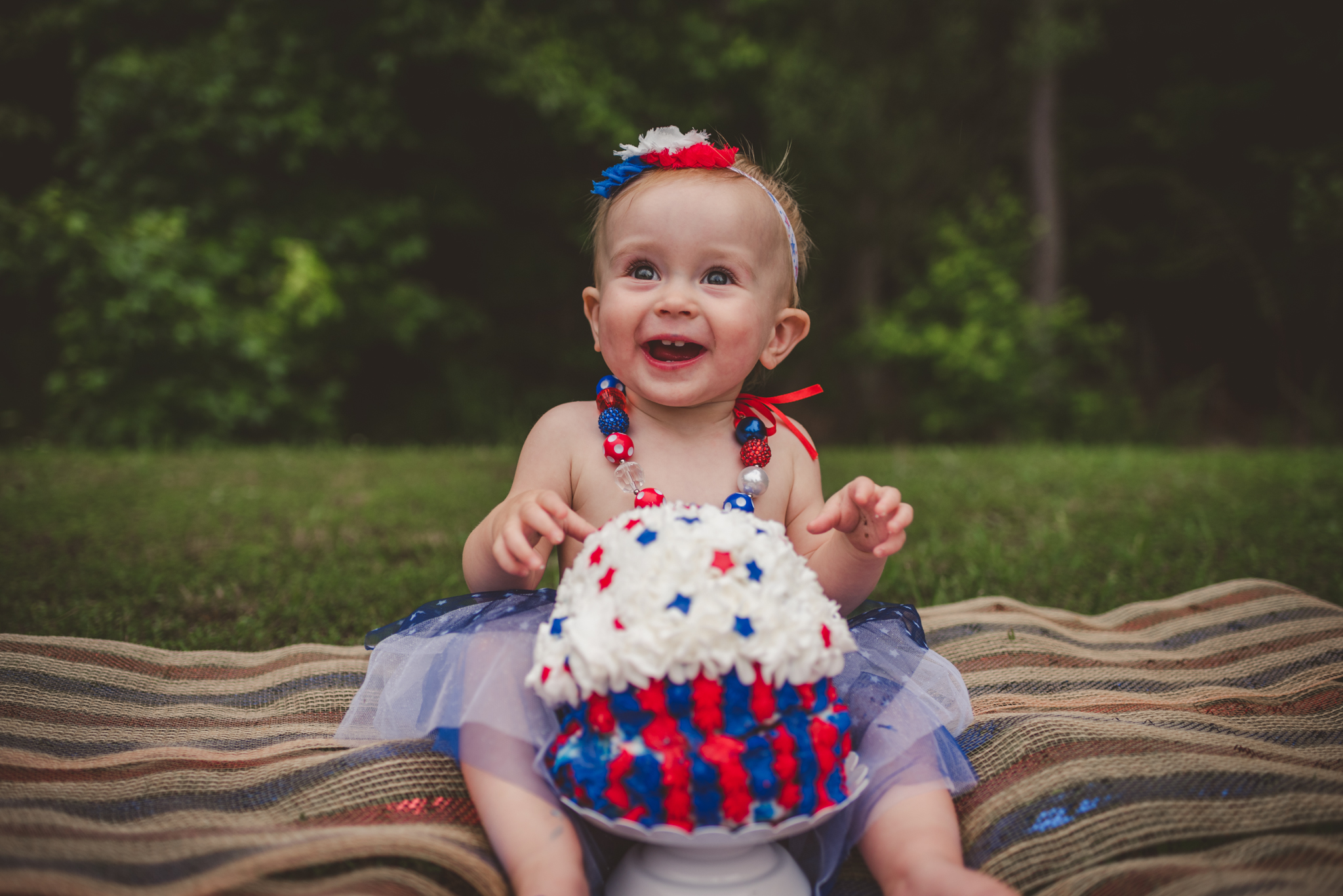 This little girl is getting ready to eat cake for her one year old fourth of July cake smash session with Rose Trail Images in Rolesville, North Carolina.