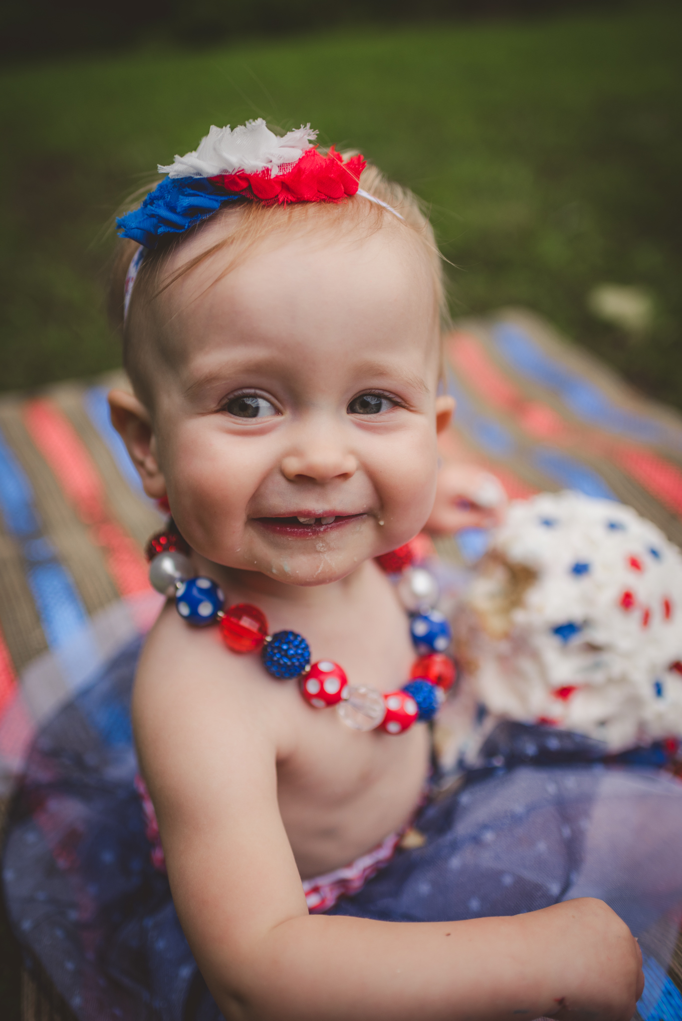 This little girl is so happy to eat her red, white and blue cake for her one year old fourth of July cake smash session with Rose Trail Images in Rolesville, North Carolina.