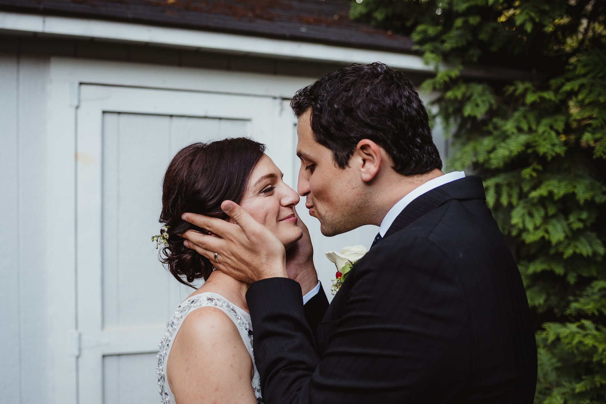 The groom holds his new brides face as he goes in to kiss her after their intimate wedding ceremony that took place in their backyard in downtown Raleigh, North Carolina, photo by Rose Trail Images.