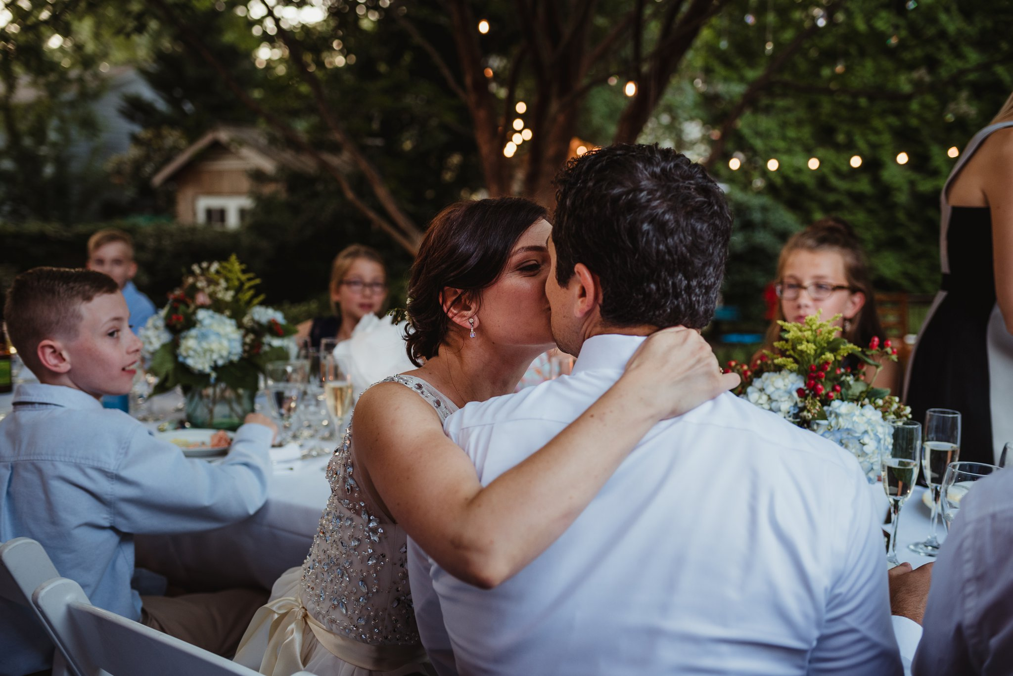 The bride and groom kiss during their intimate wedding reception in their backyard in Raleigh under the market lights, photo by Rose Trail Images.