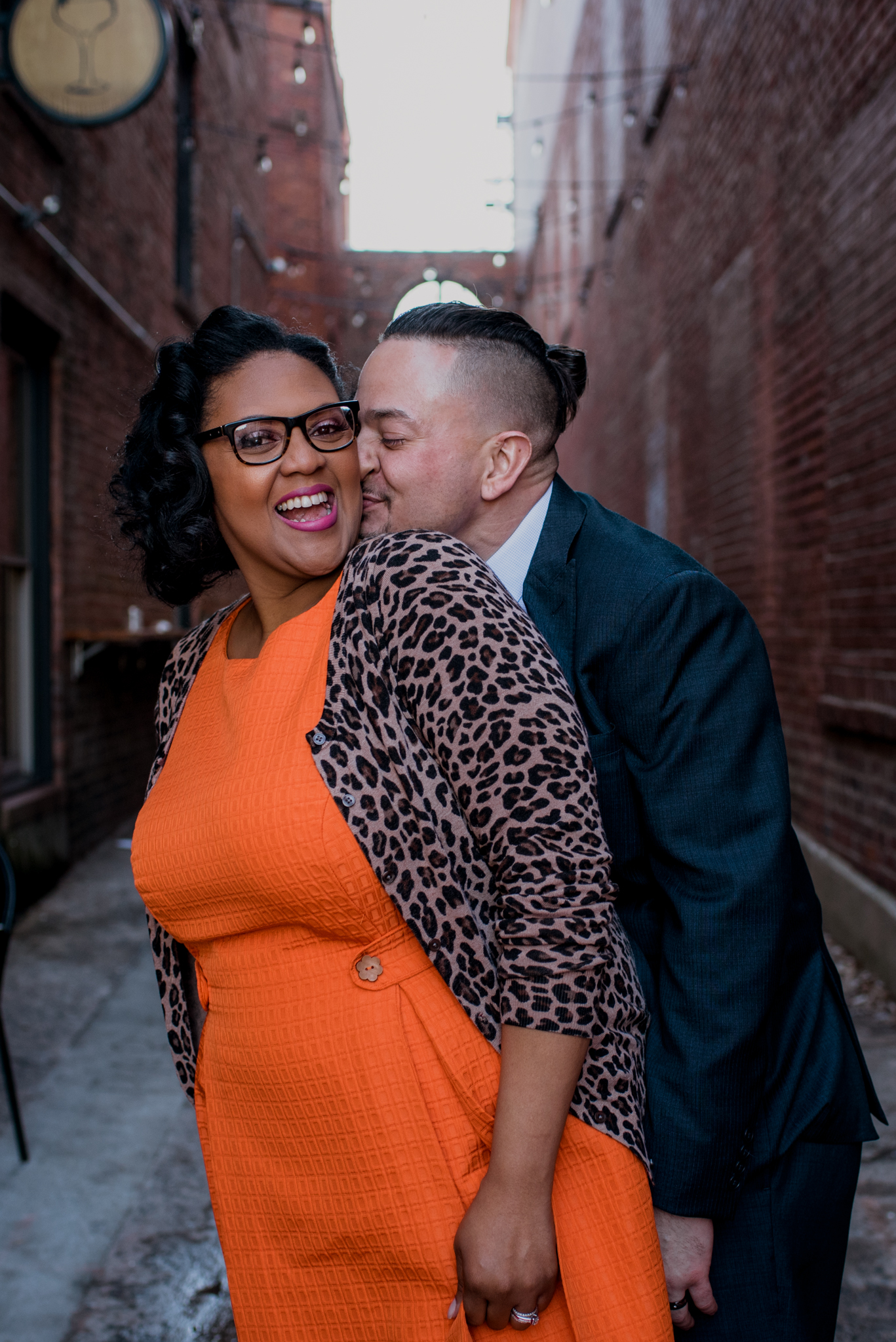 The husband kisses his wife's cheek in an alley way outside of The Durham Hotel in Durham, North Carolina, image by Rose Trail Images.