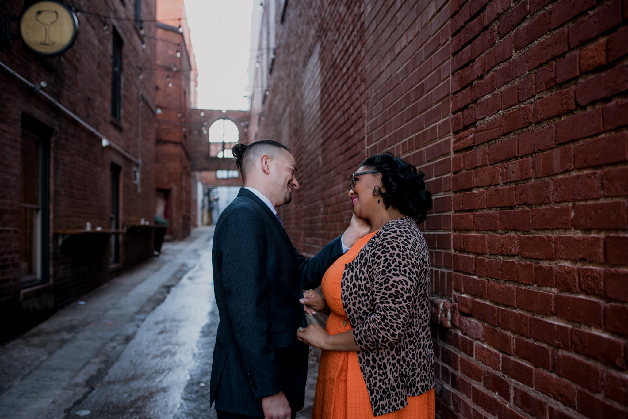 The husband and wife stand close in an alley way outside of The Durham Hotel in Durham, North Carolina, image by Rose Trail Images.