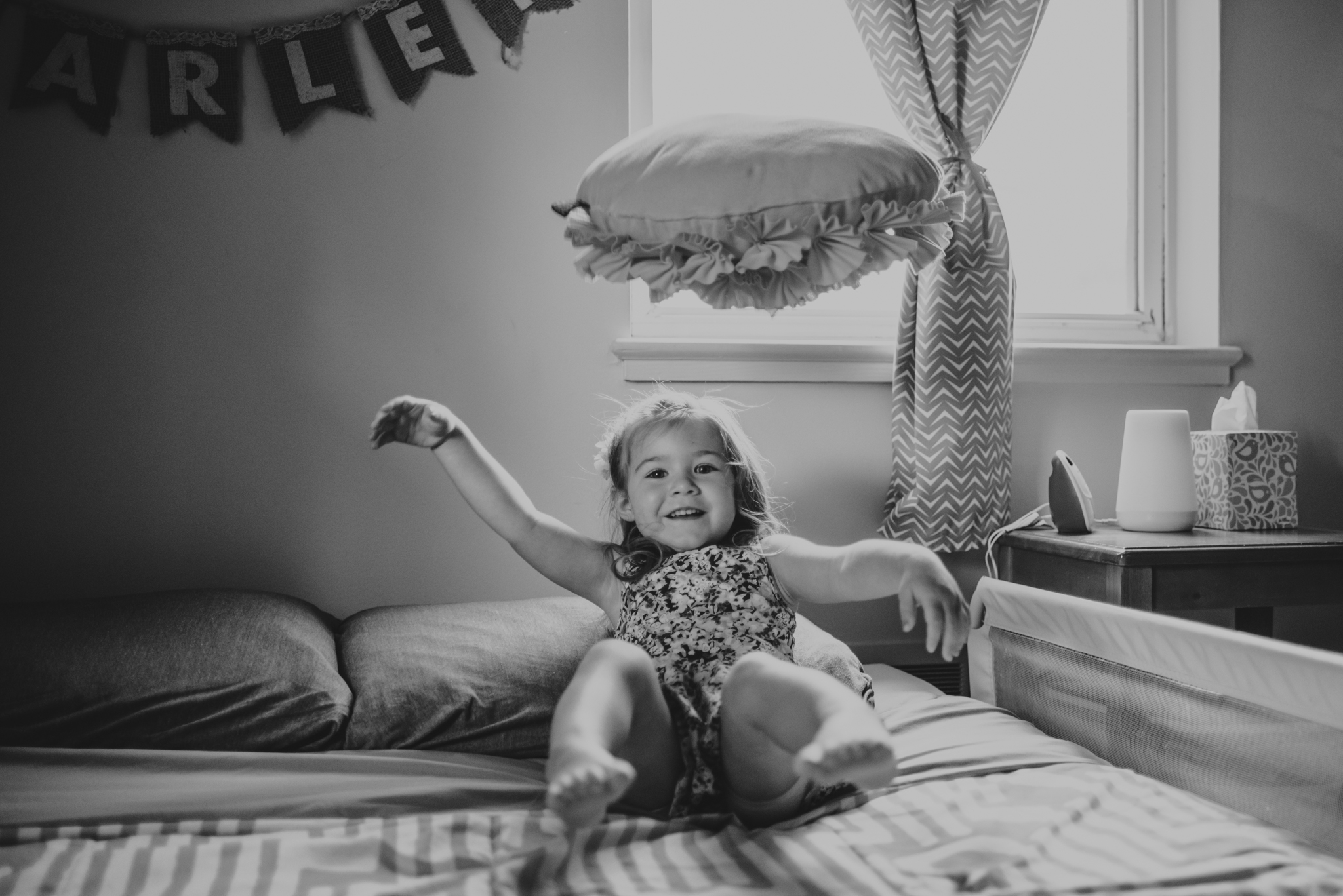 The little girl giggles on her bed during their lifestyle session at home in Wake Forest with Rose Trail Images.
