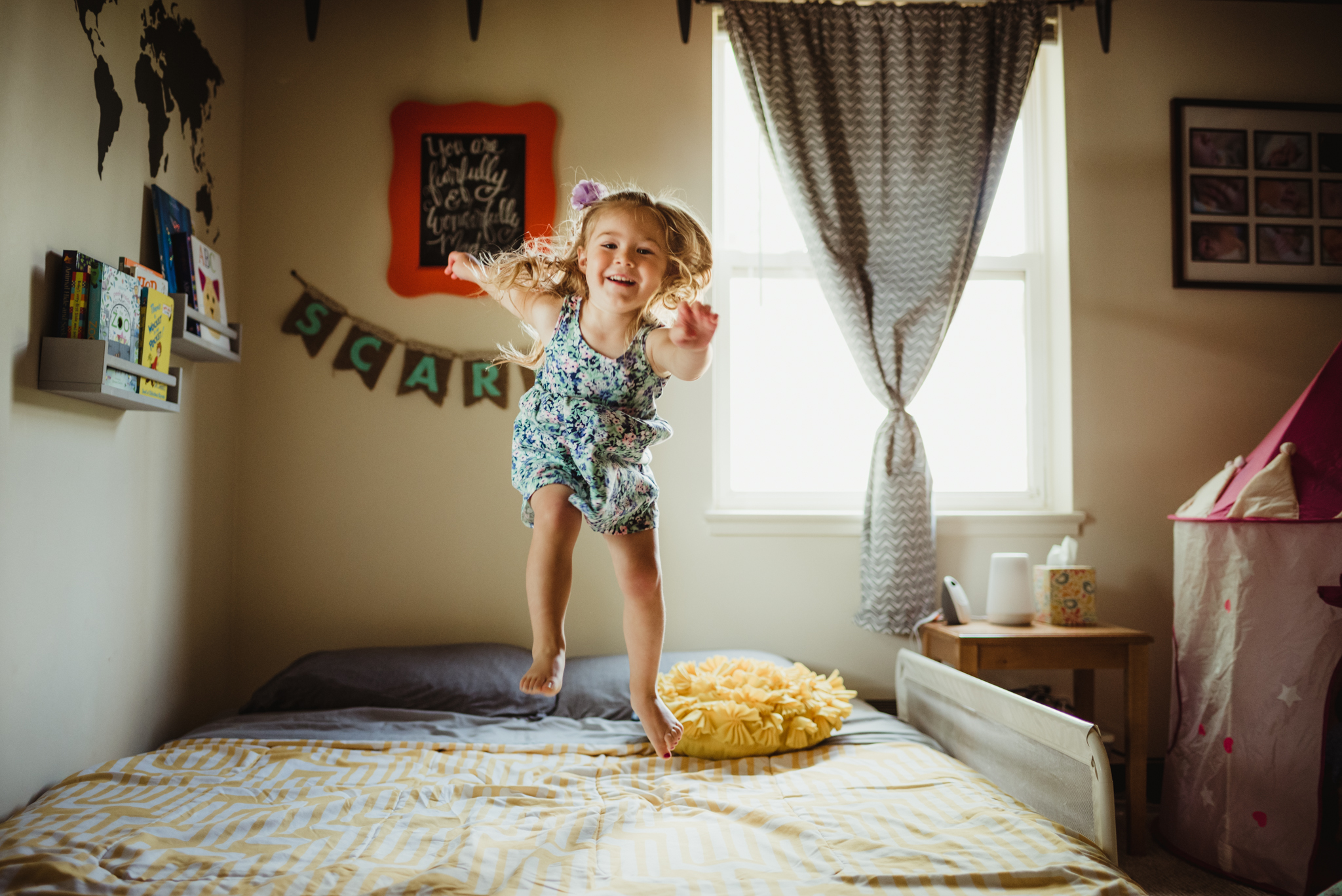 The little girl jumps up and down on her bed during their lifestyle session at home in Wake Forest with Rose Trail Images.