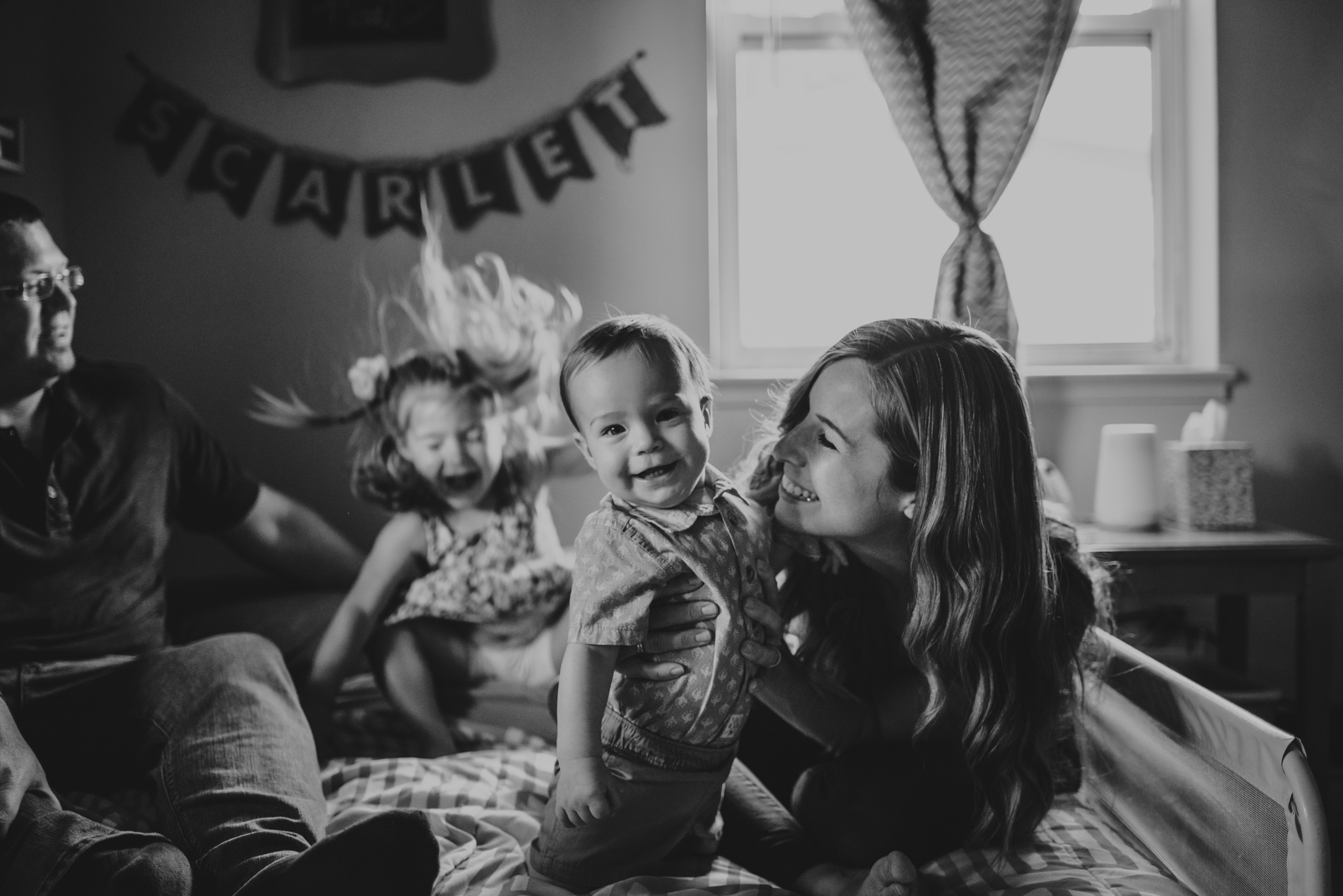 Mom laughs with baby on the little girl's bed during their lifestyle session at home in Wake Forest with Rose Trail Images.