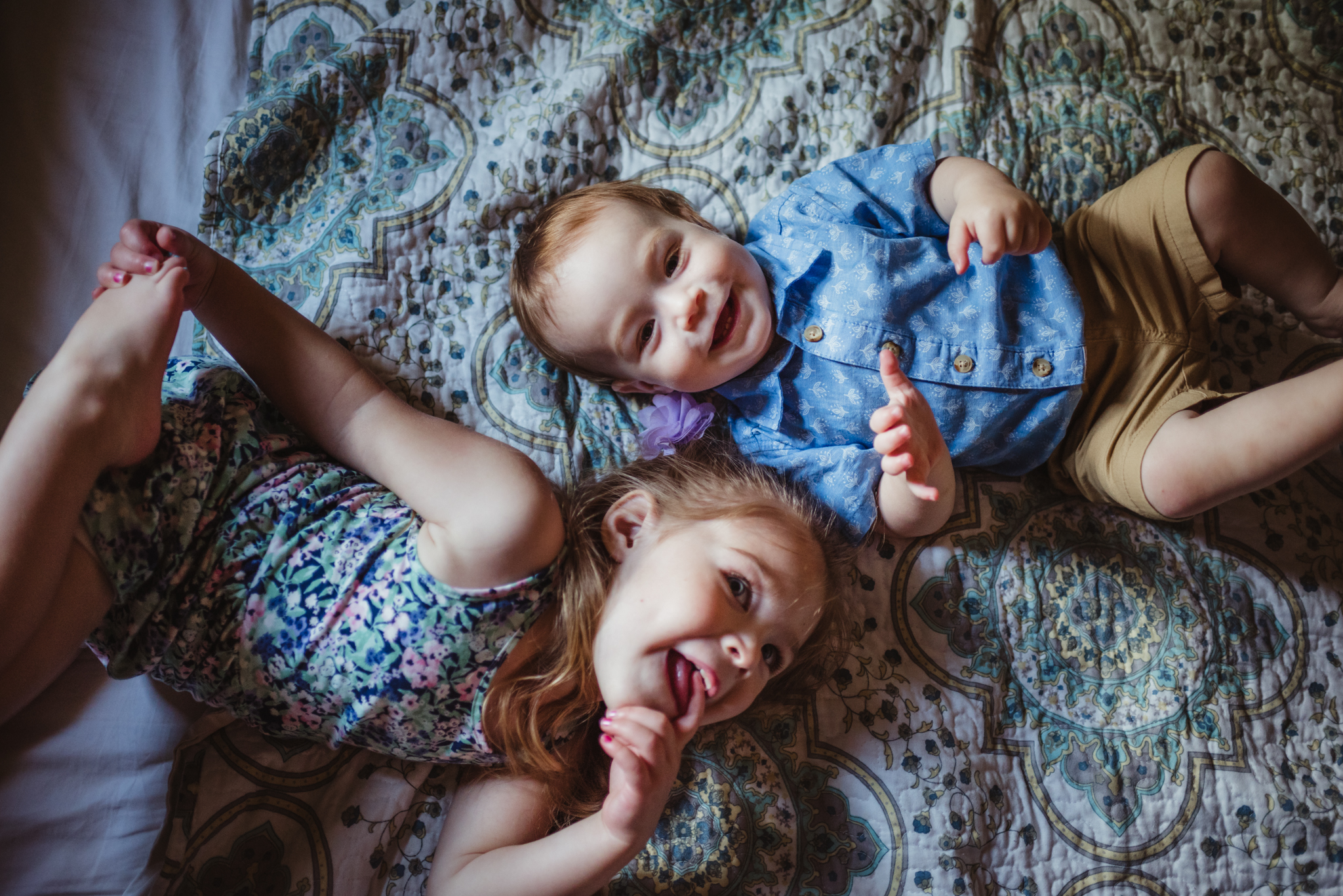 The kids lay together on their parents' bed during their lifestyle session at home in Wake Forest with Rose Trail Images.