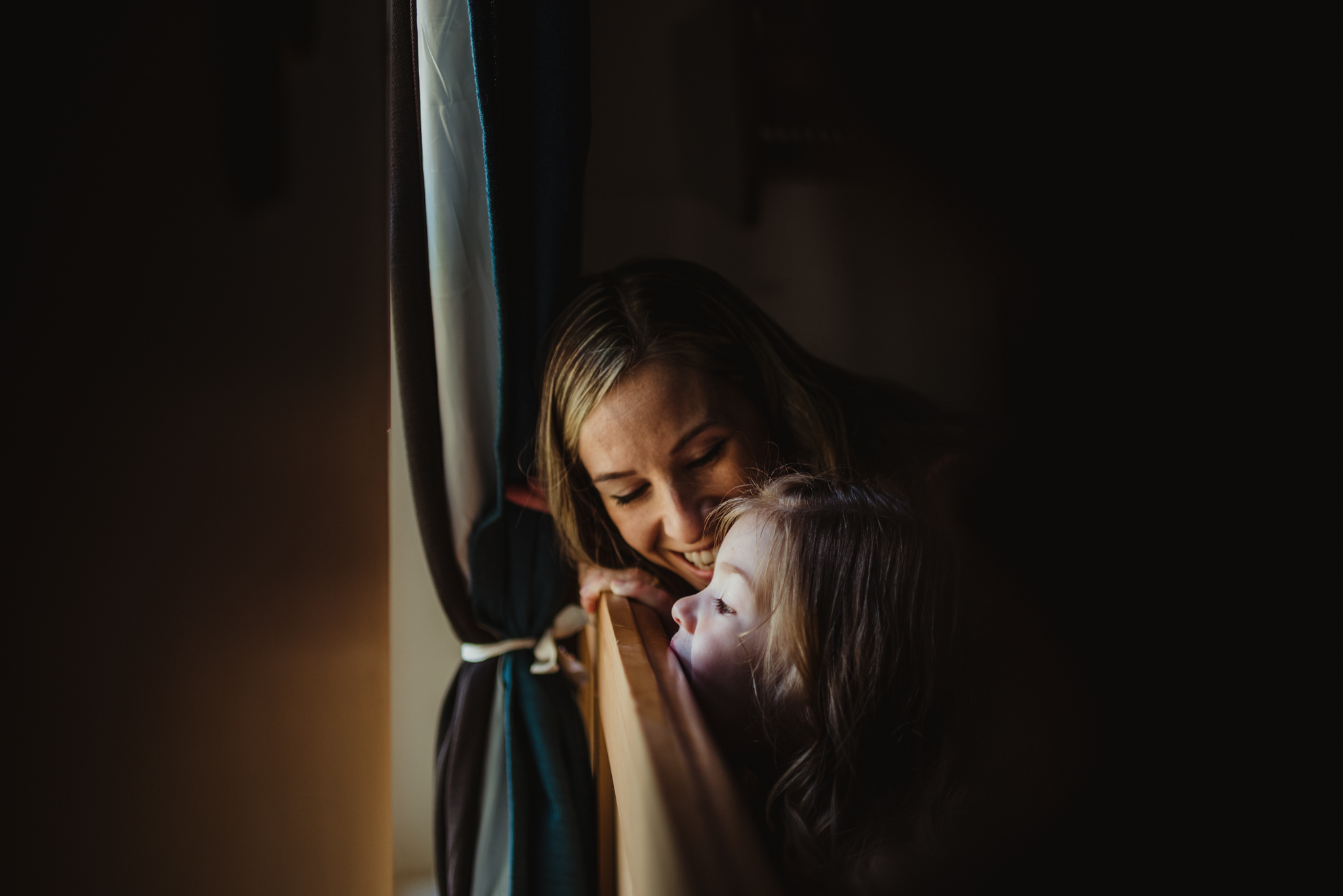 Mom watches her little girl stare out the window during their lifestyle session at home in Wake Forest with Rose Trail Images.