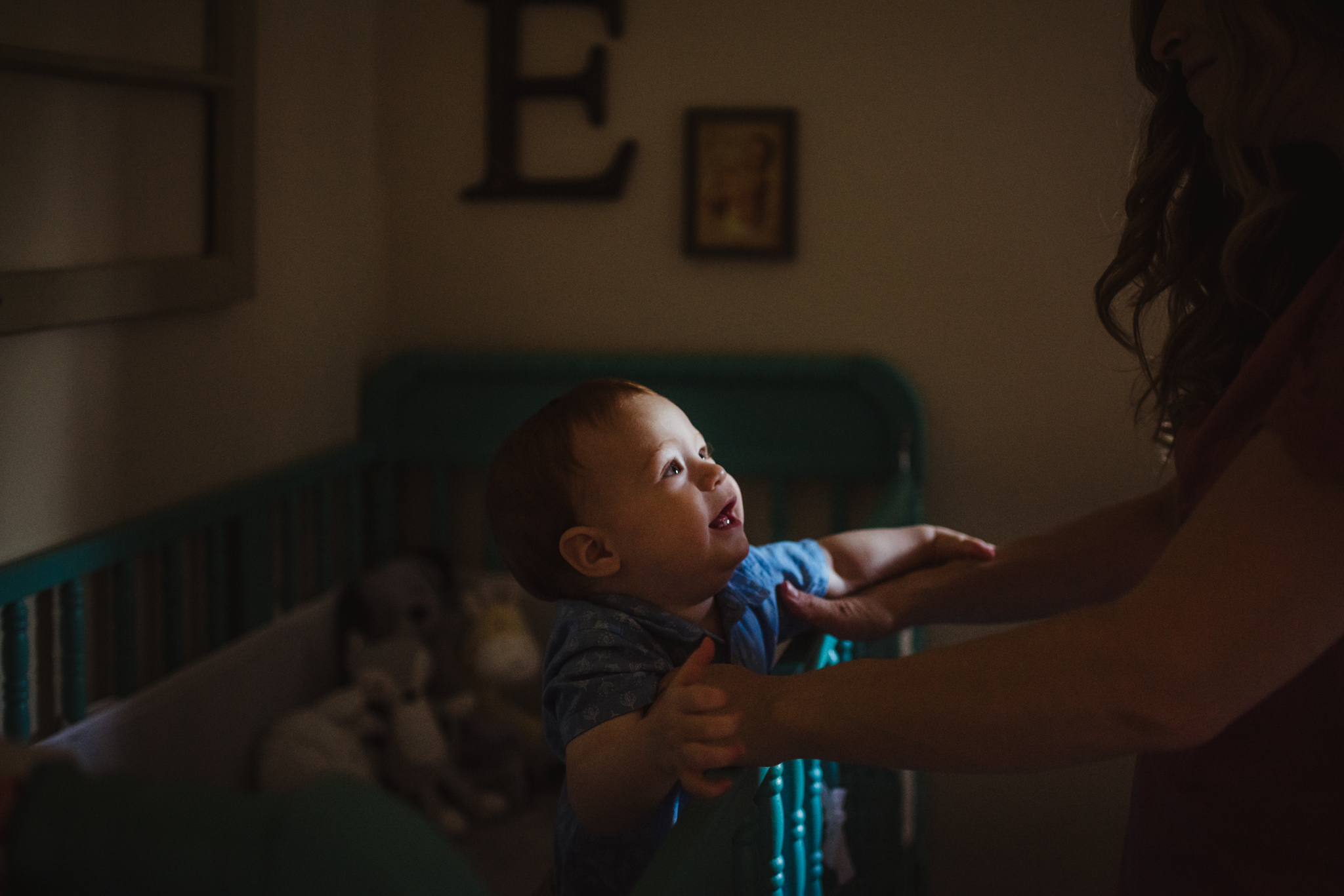 The baby reaches for Mom in his crib during their lifestyle session at home in Wake Forest with Rose Trail Images.