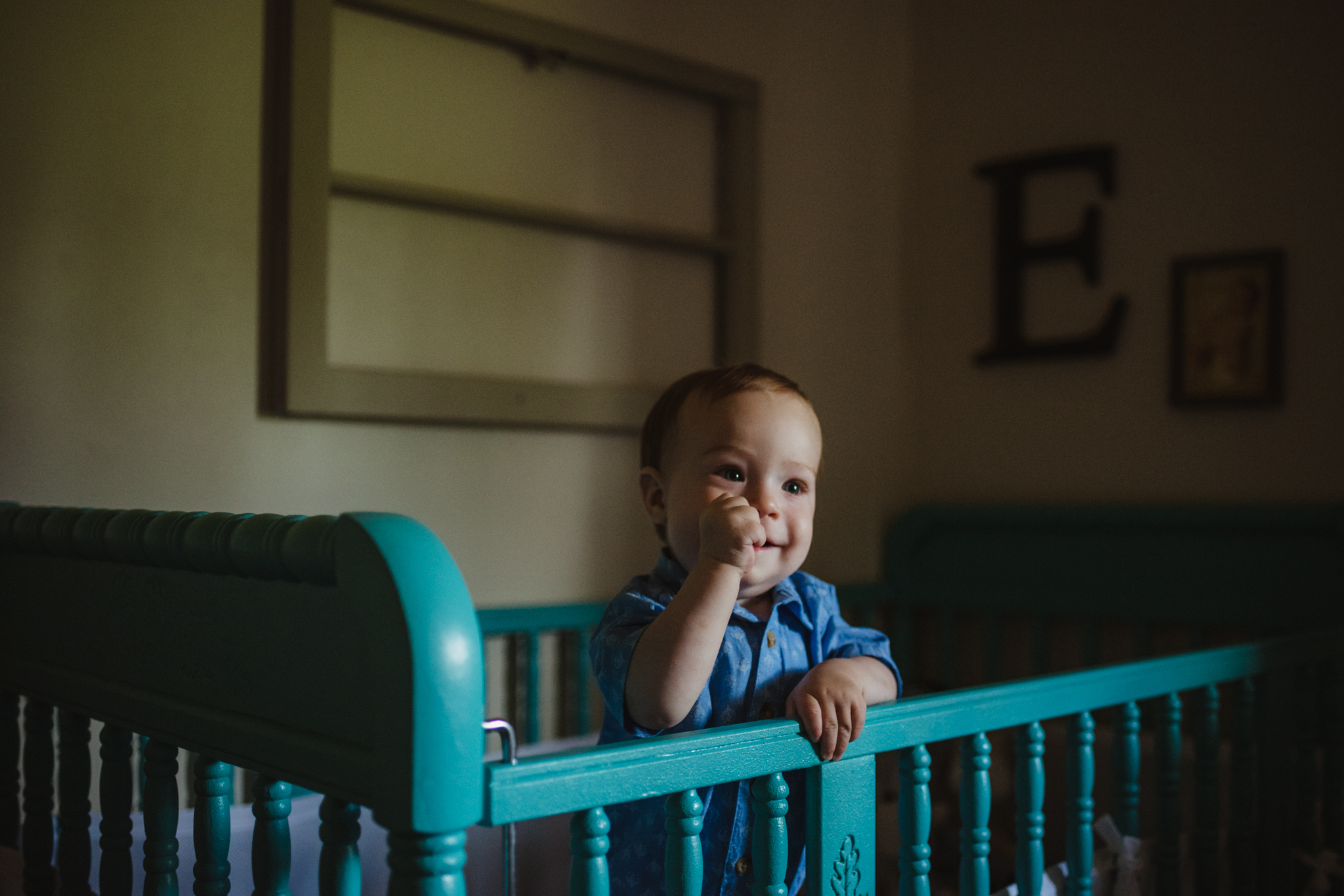 The baby stands in his crib during their lifestyle session at home in Wake Forest with Rose Trail Images.