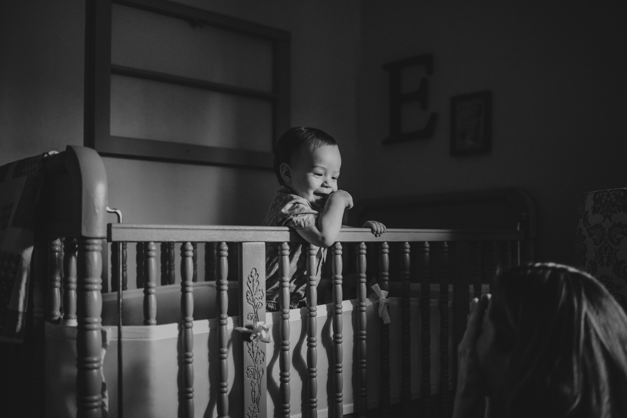 The baby giggles at his Mom while in his crib during their lifestyle session at home in Wake Forest with Rose Trail Images.