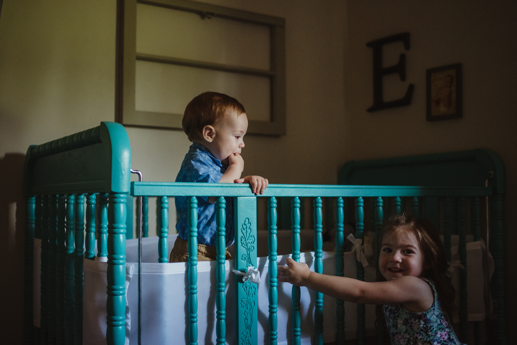 The baby giggles at his sister while in his crib during their lifestyle session at home in Wake Forest with Rose Trail Images.