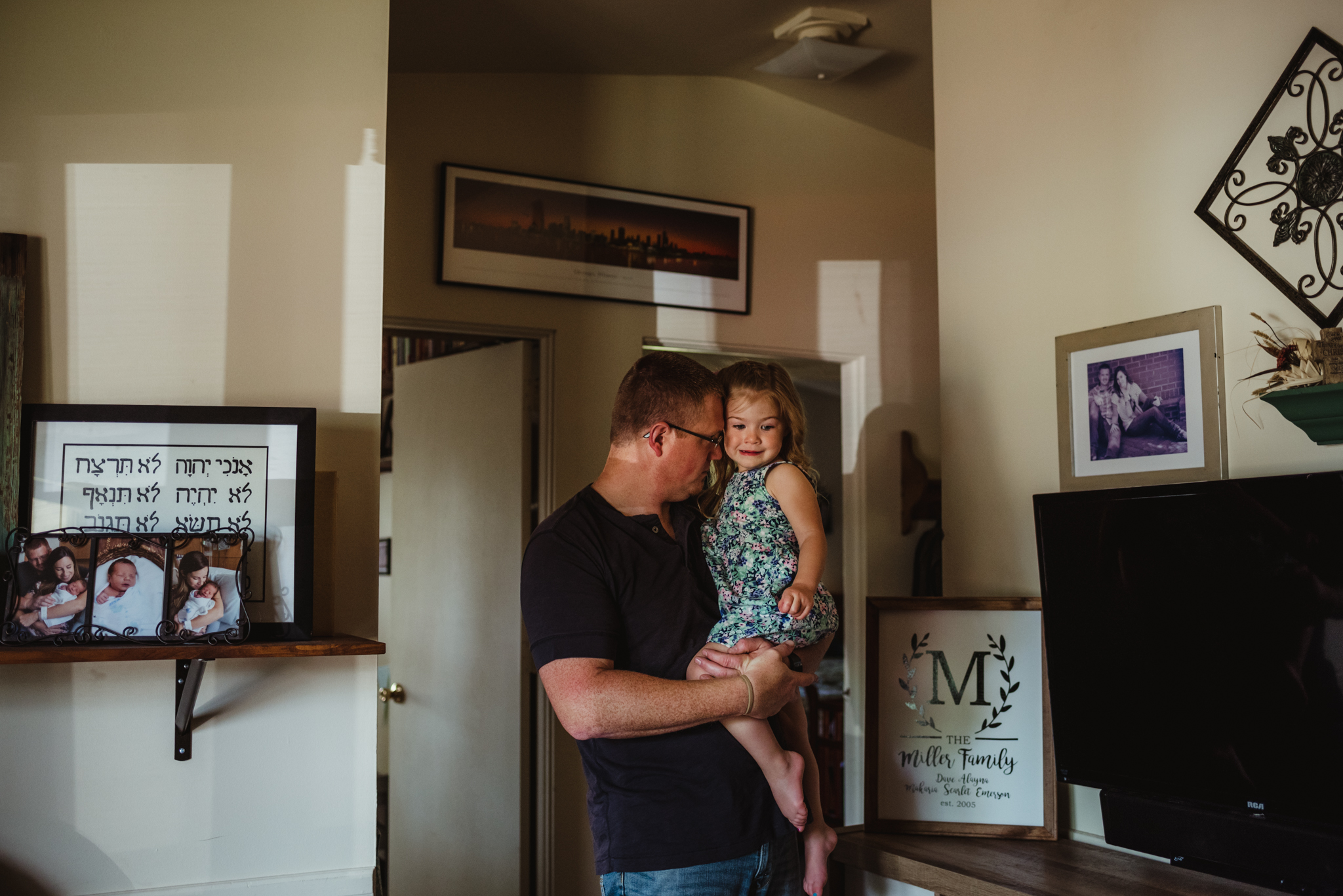 Daddy carries the little girl into the living room during their lifestyle session at home in Wake Forest with Rose Trail Images.