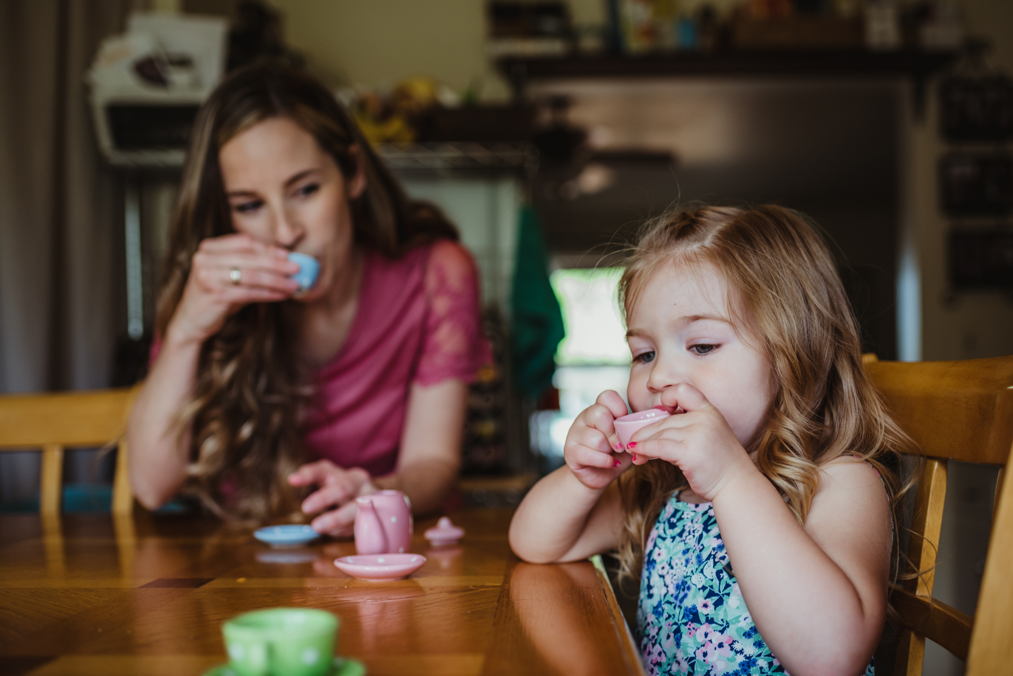 The little girl and Mom have tea time in the kitchen during their lifestyle session at home in Wake Forest with Rose Trail Images.