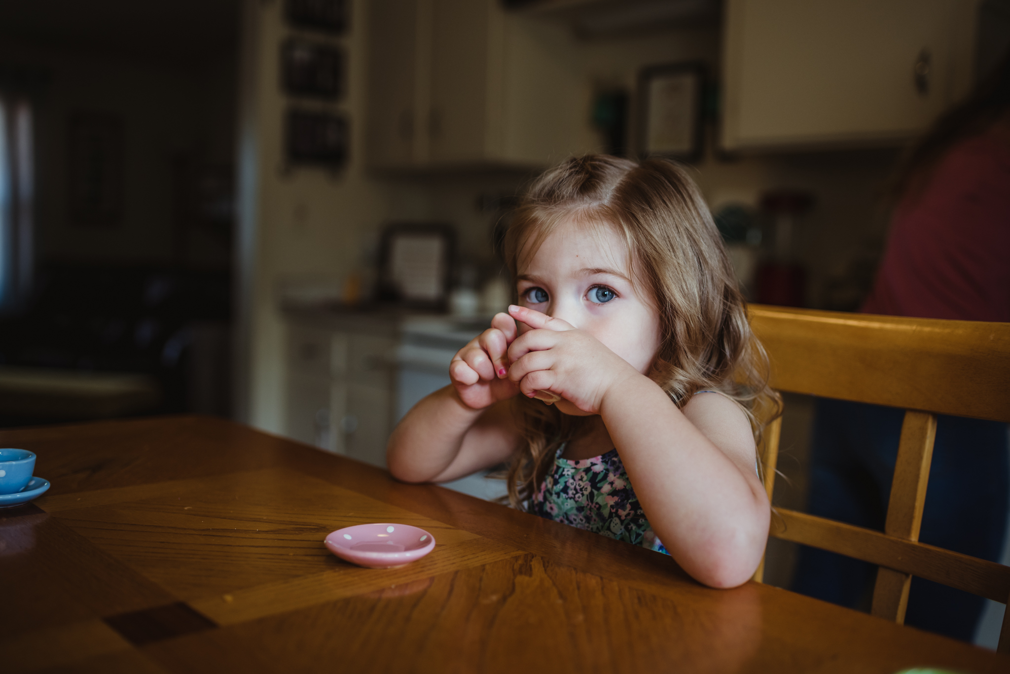 The little girl sips her tea in the kitchen during their lifestyle session at home in Wake Forest with Rose Trail Images.
