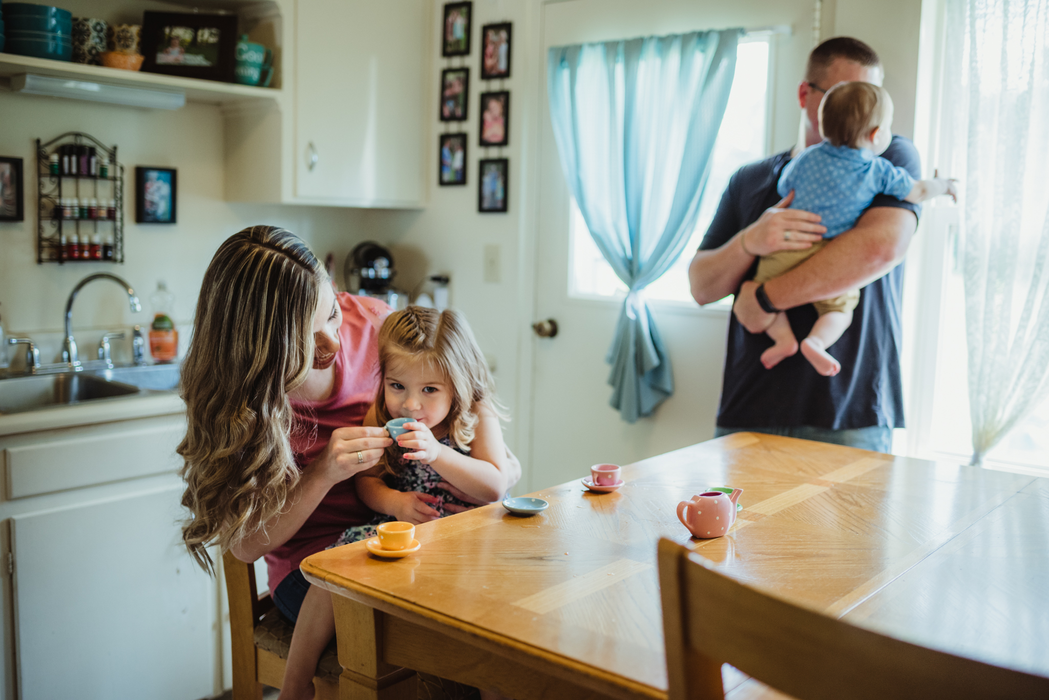 The little girl and Mom have tea time together with the family in the kitchen during their lifestyle session at home in Wake Forest with Rose Trail Images.