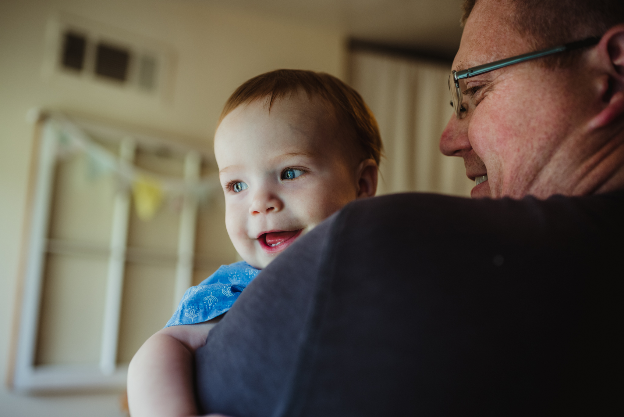 The baby giggles over Dad's shoulder in the kitchen during their lifestyle session at home in Wake Forest with Rose Trail Images.