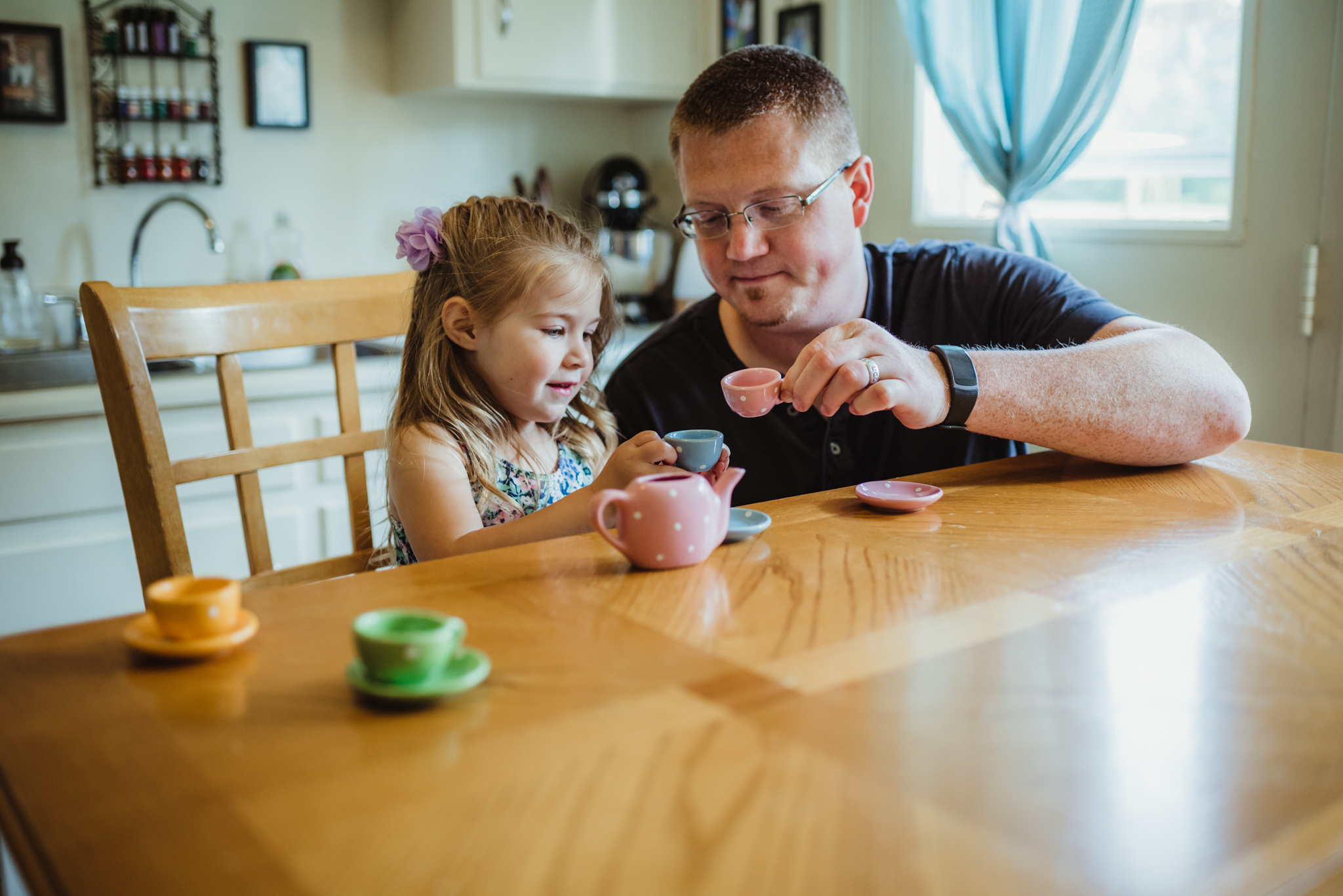 The little girl and Dad have tea time in the kitchen during their lifestyle session at home in Wake Forest with Rose Trail Images.