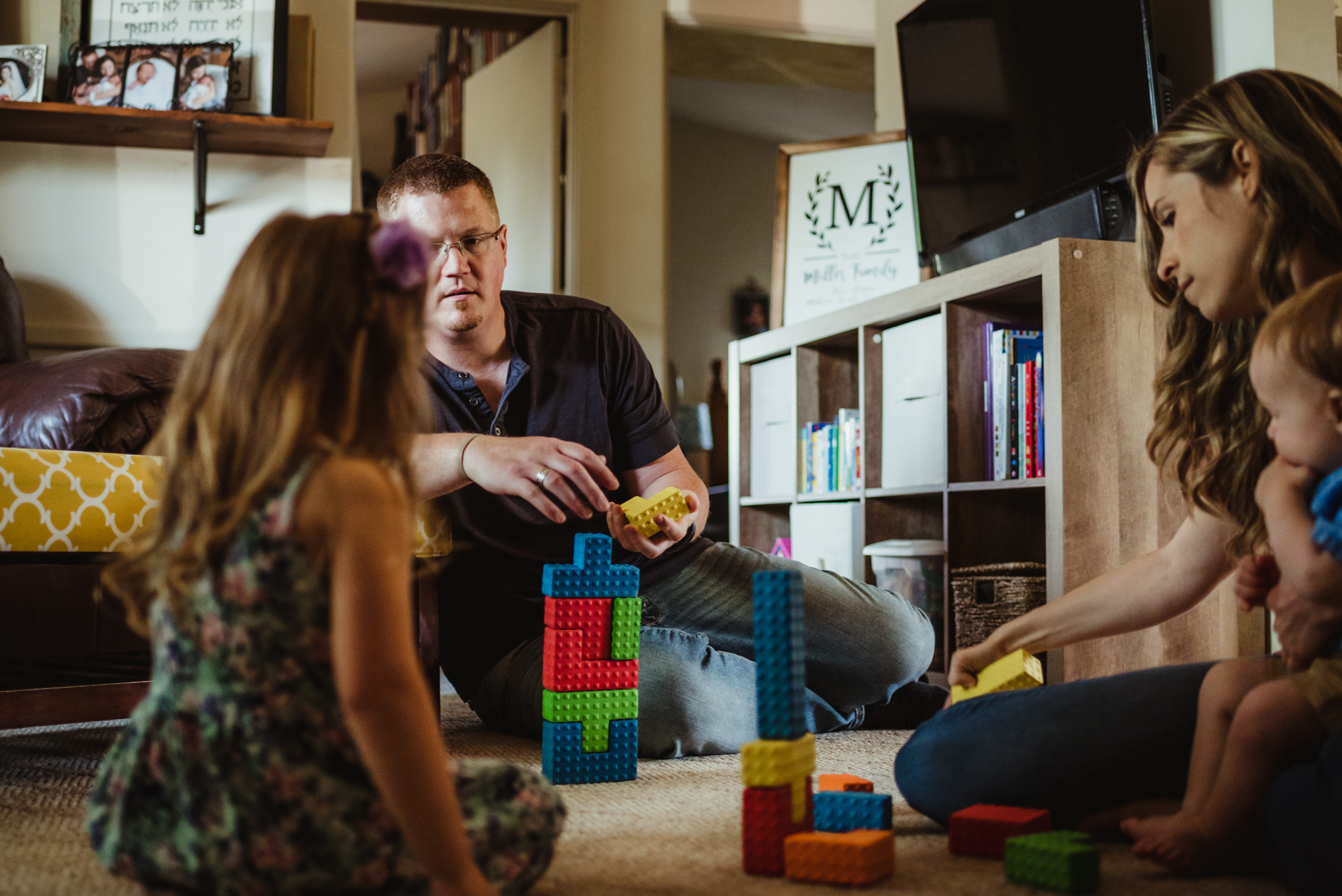 The family plays blocks together in the living room during their lifestyle session at home in Wake Forest with Rose Trail Images.