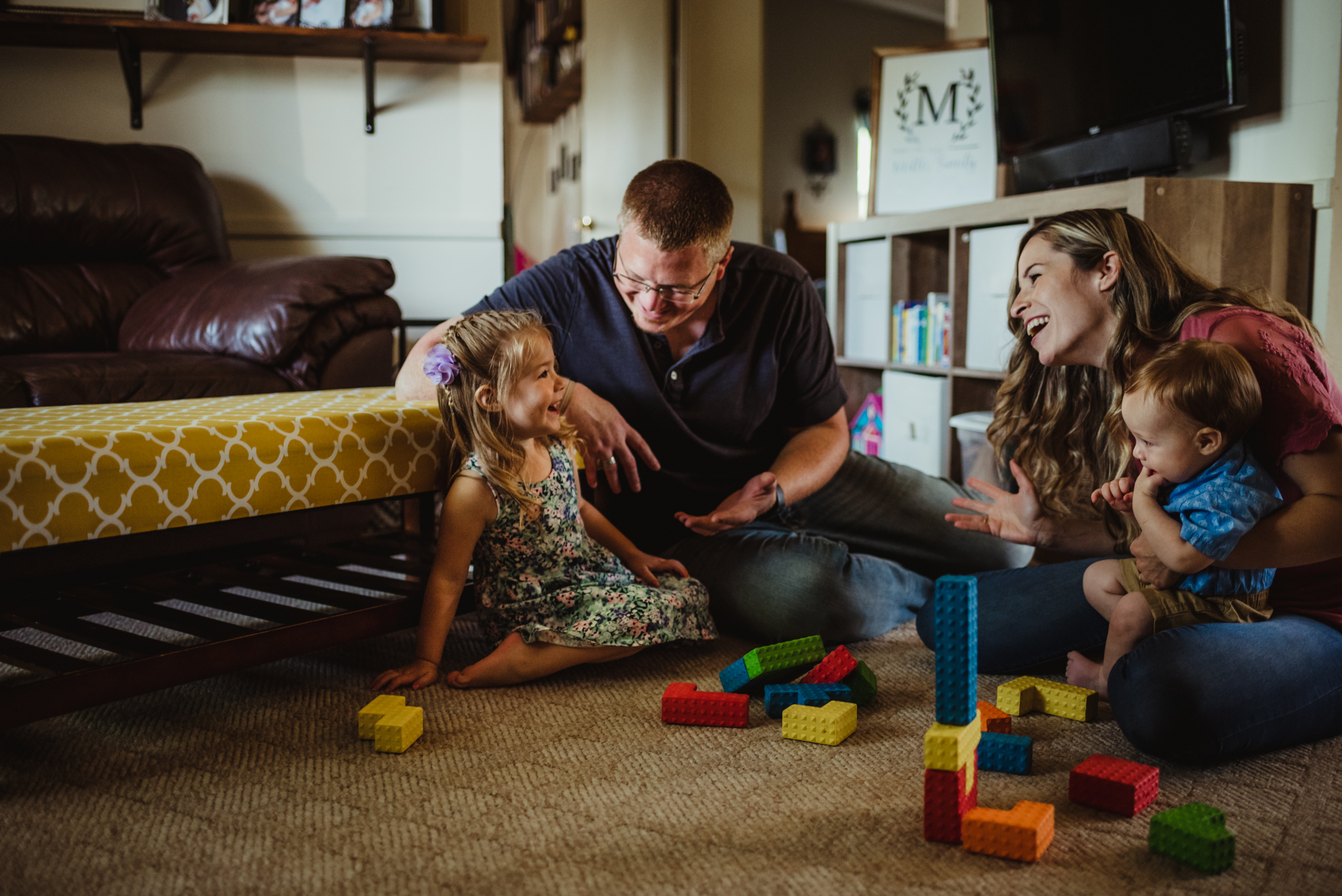 The family laughs while playing blocks together in the living room during their lifestyle session at home in Wake Forest with Rose Trail Images.