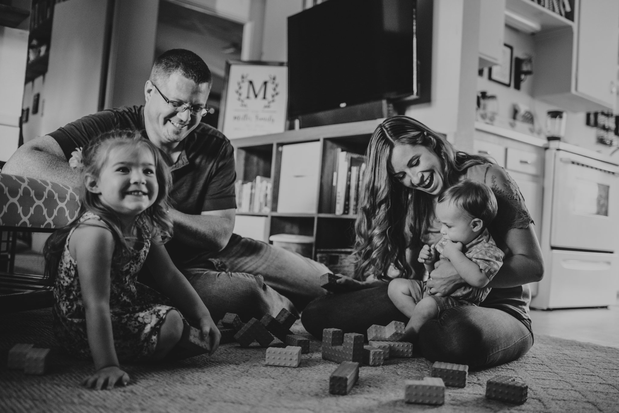 The family knocks over block towers together in the living room during their lifestyle session at home in Wake Forest with Rose Trail Images.