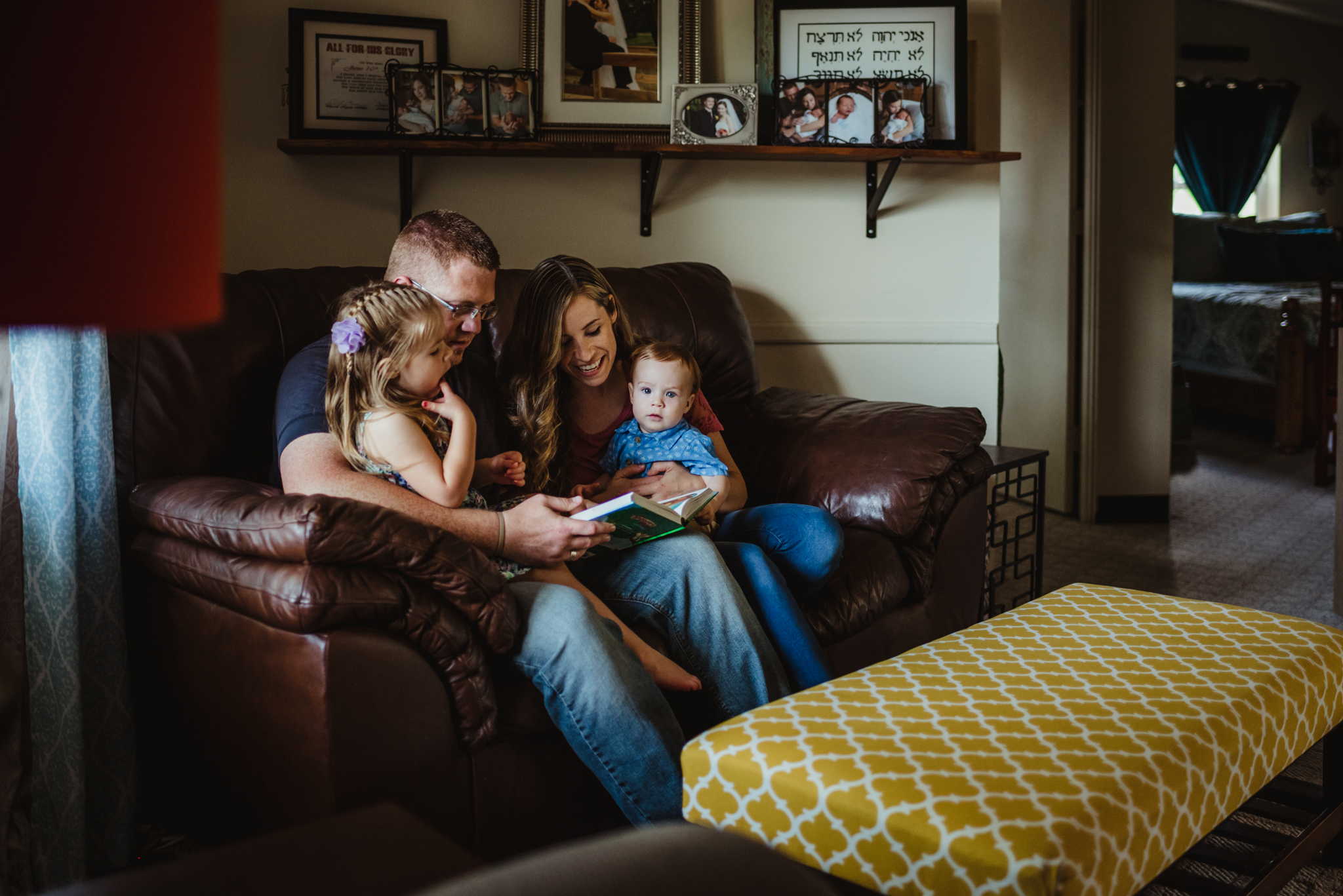 The family has Bible time together on the couch during their lifestyle session at home in Wake Forest with Rose Trail Images.