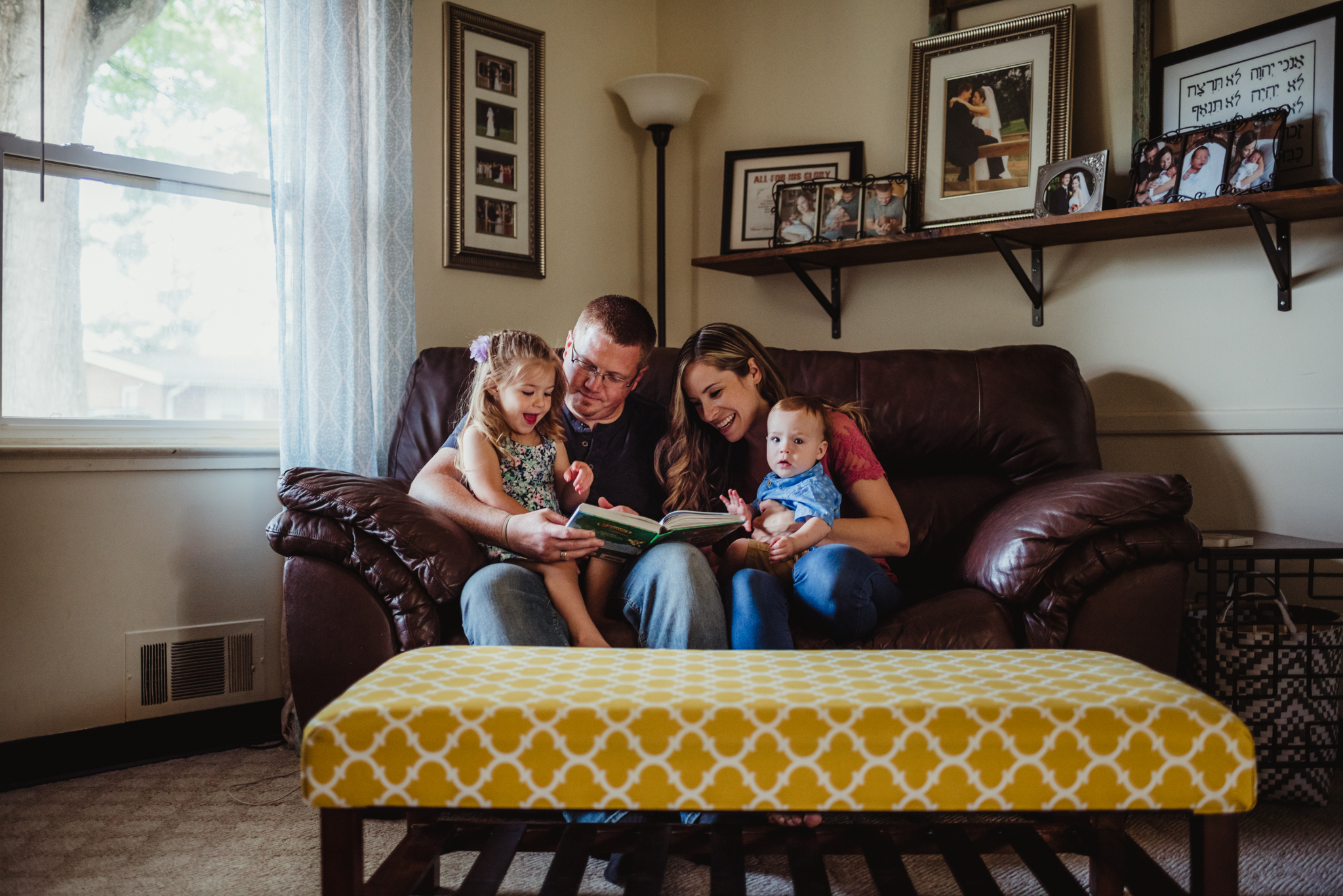 The family has story time together on the couch in the living room during their lifestyle session at home in Wake Forest with Rose Trail Images.