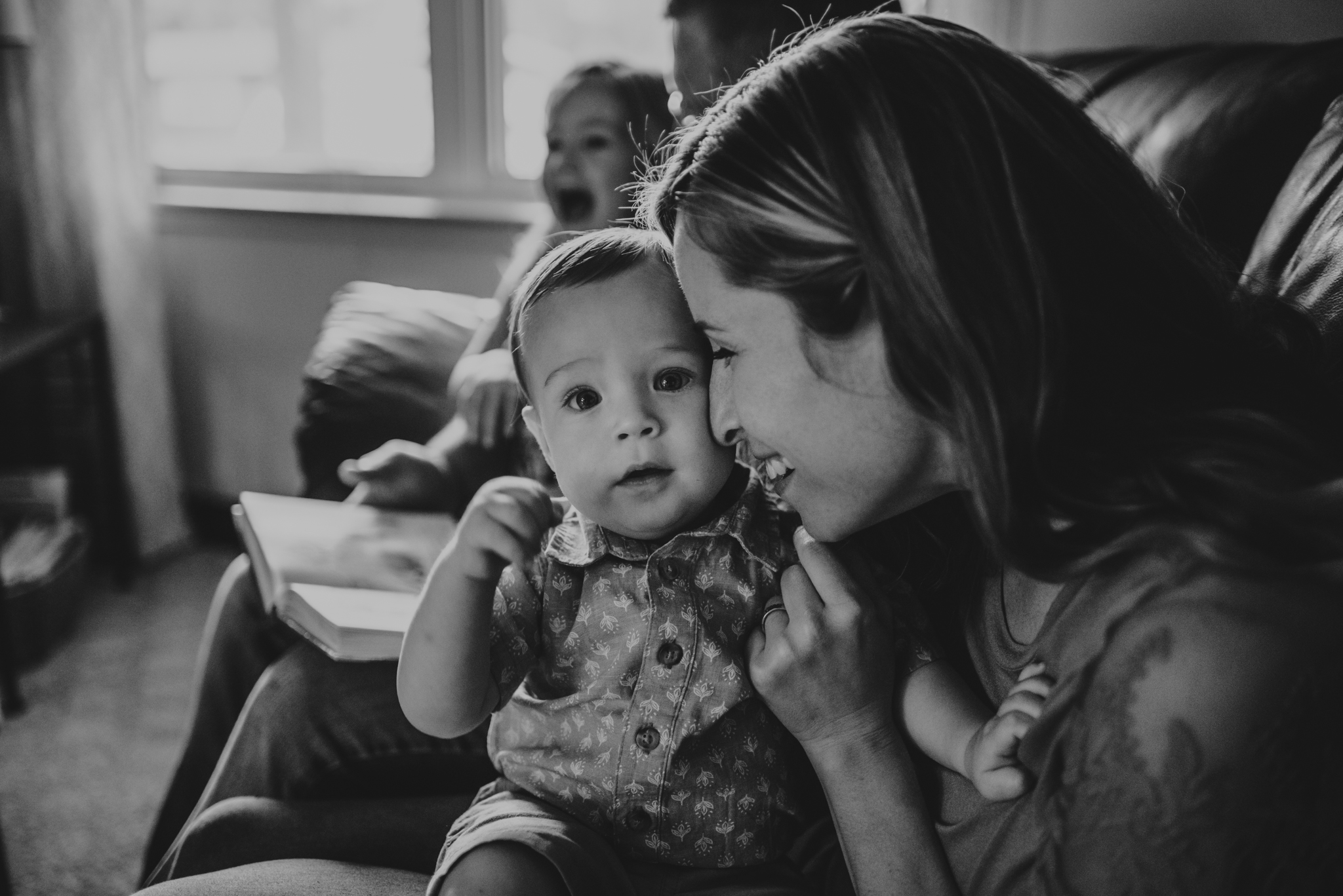 Mommy snuggles baby during story time together on the couch during their lifestyle session at home in Wake Forest with Rose Trail Images.